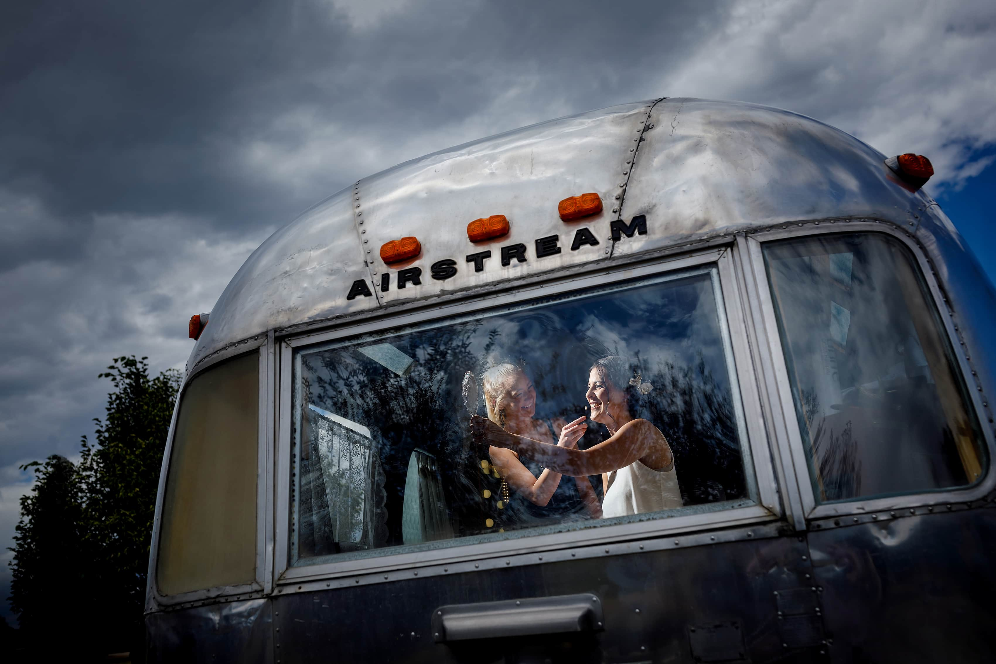 bride has her makeup done in airstream trailer while getting ready for wedding at Lionsgate Event Center