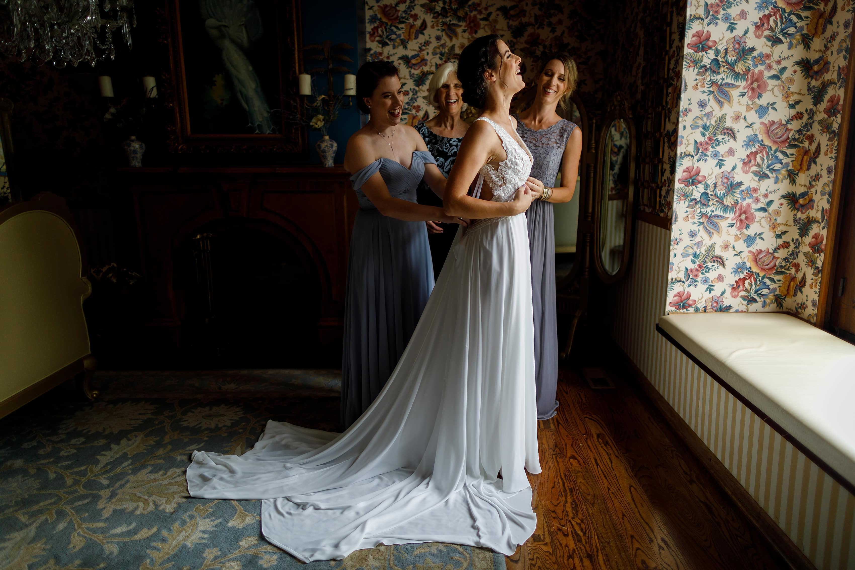 bride and sisters and mom put wedding dress on in bridal suite at Lionsgate Event Center