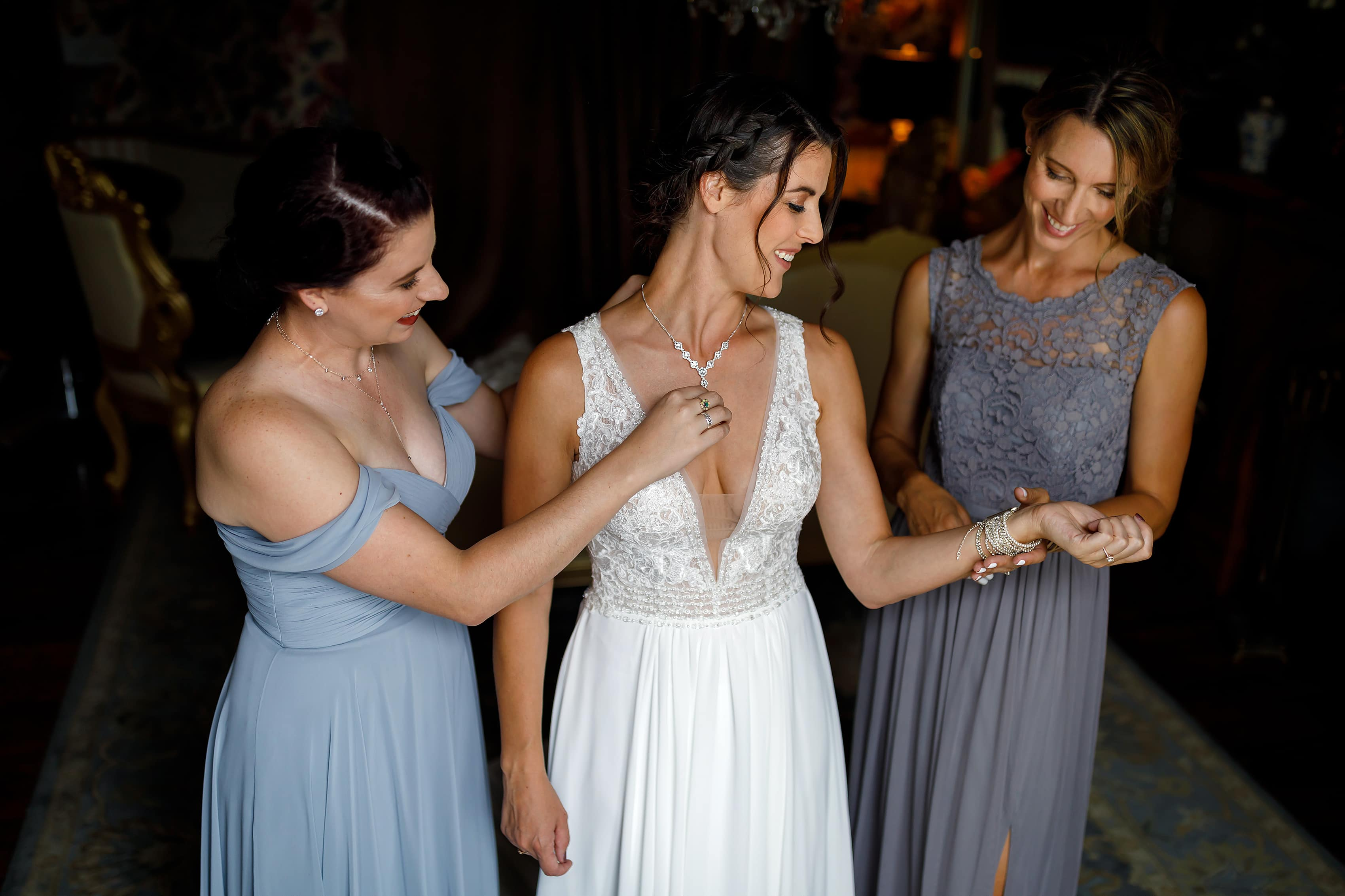 bride's sisters put jewelry on in bridal suite at Lionsgate Event Center