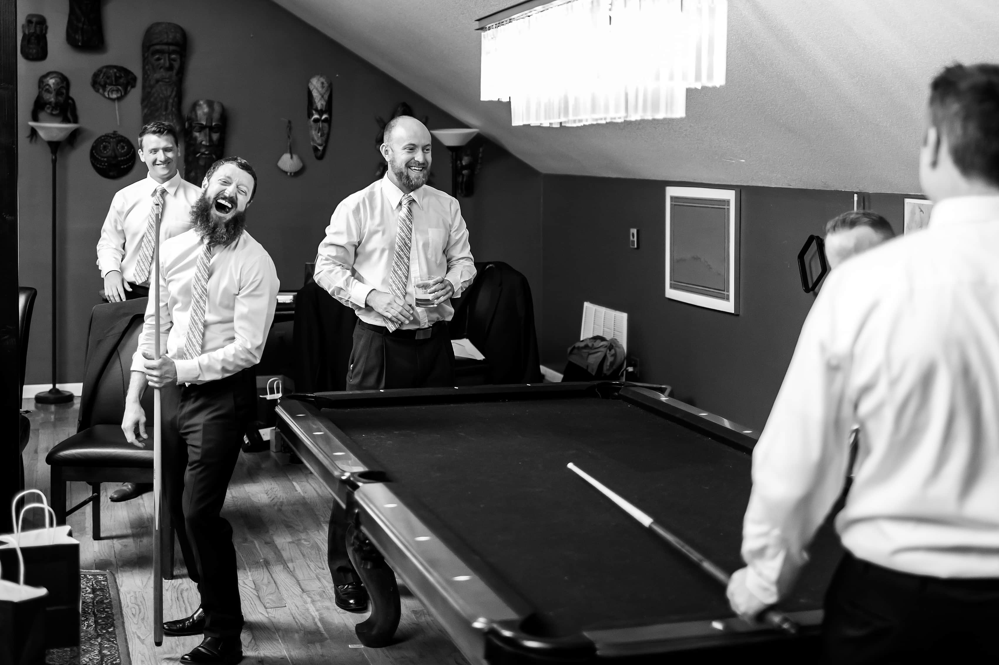 Groomsmen play pool before wedding at Lionsgate Event Center