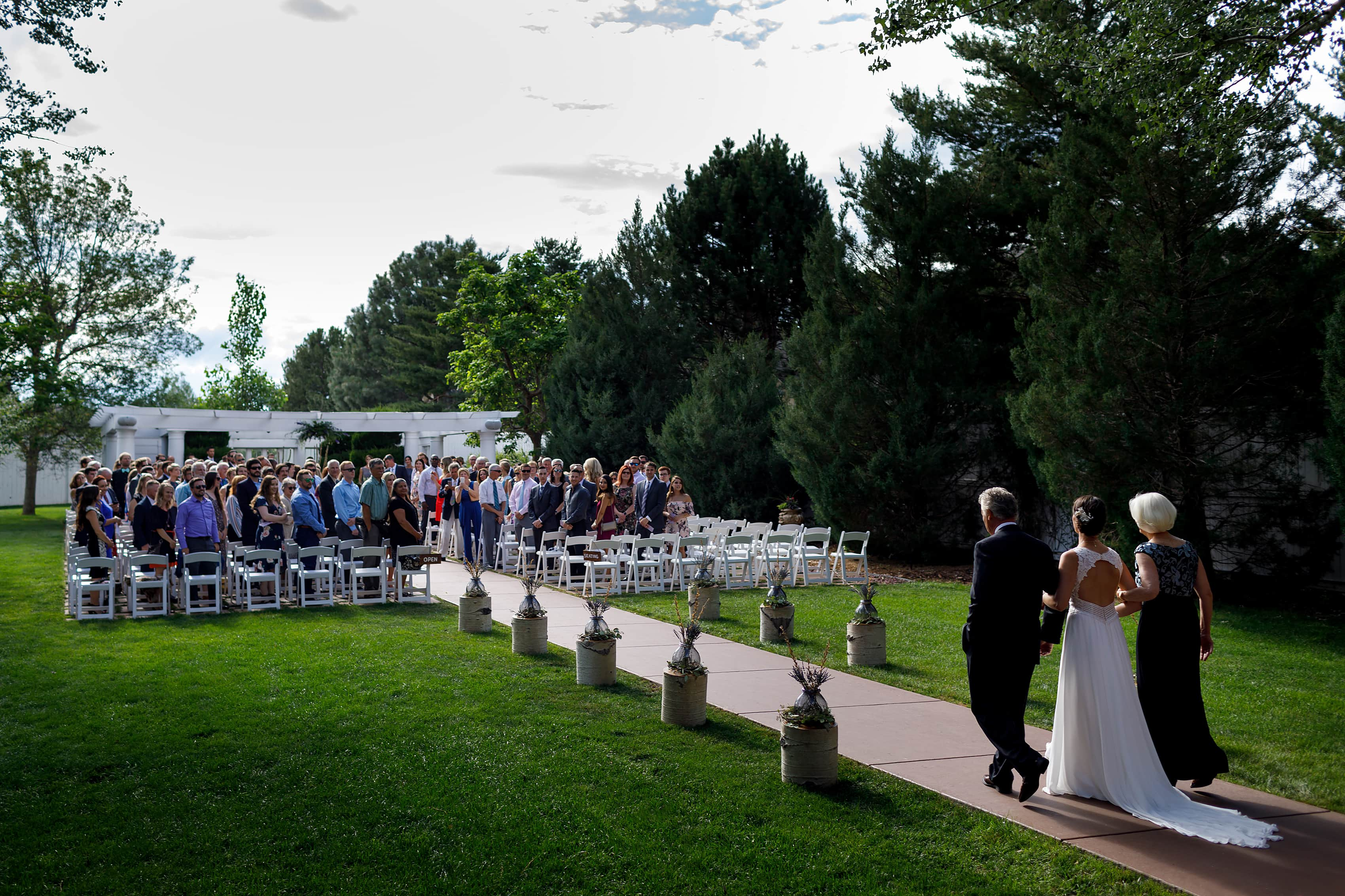bride walks out with her parents during wedding ceremony at Lionsgate Event Center wedding