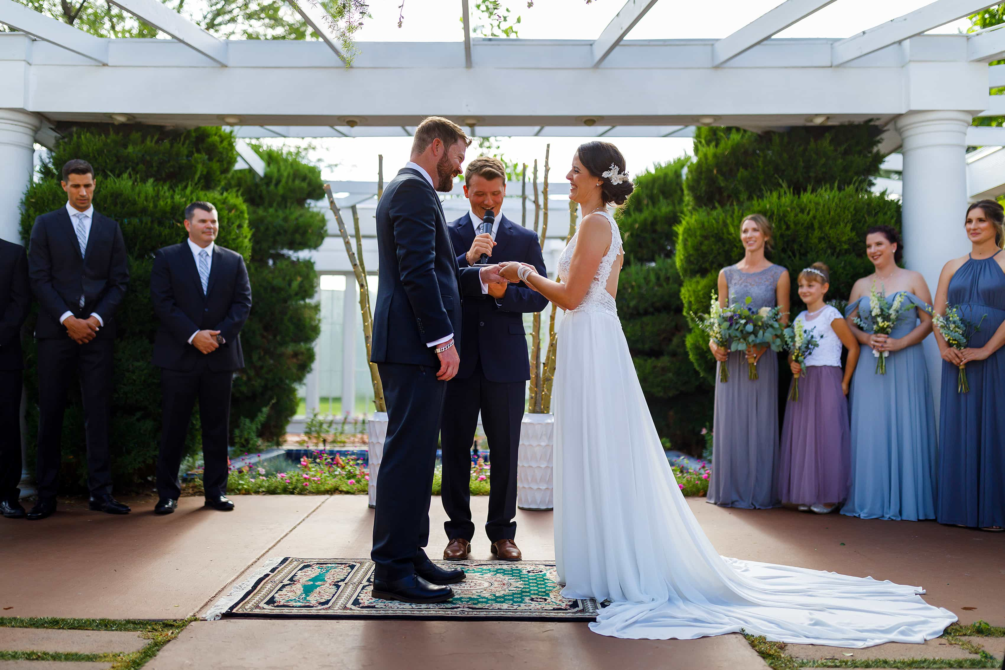 bride and groom exchange rings during outdoor wedding ceremony at Lionsgate Event Center