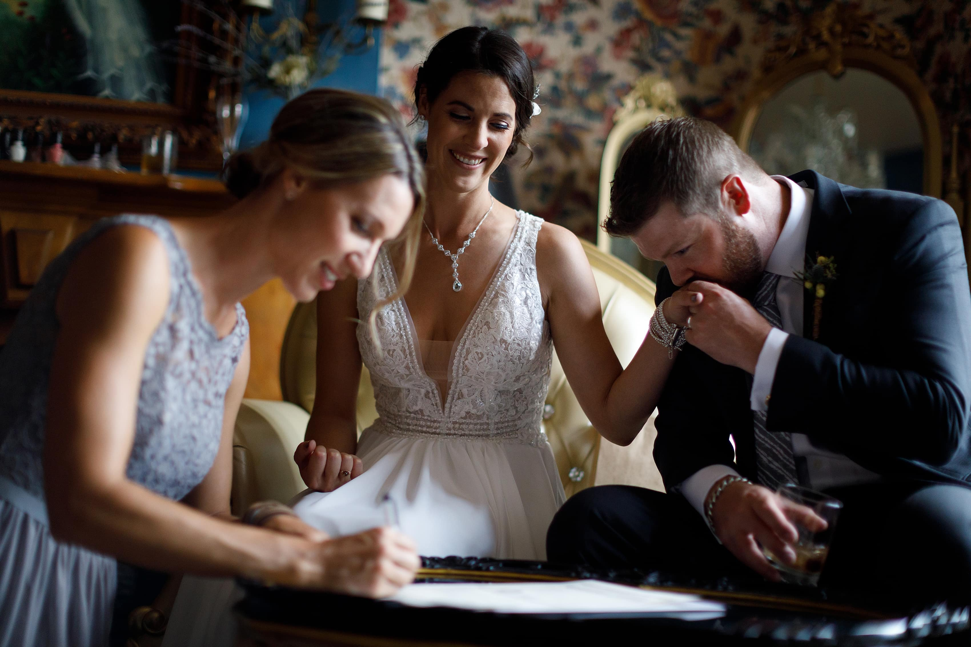 groom kisses bride's hand while sister signs marriage license
