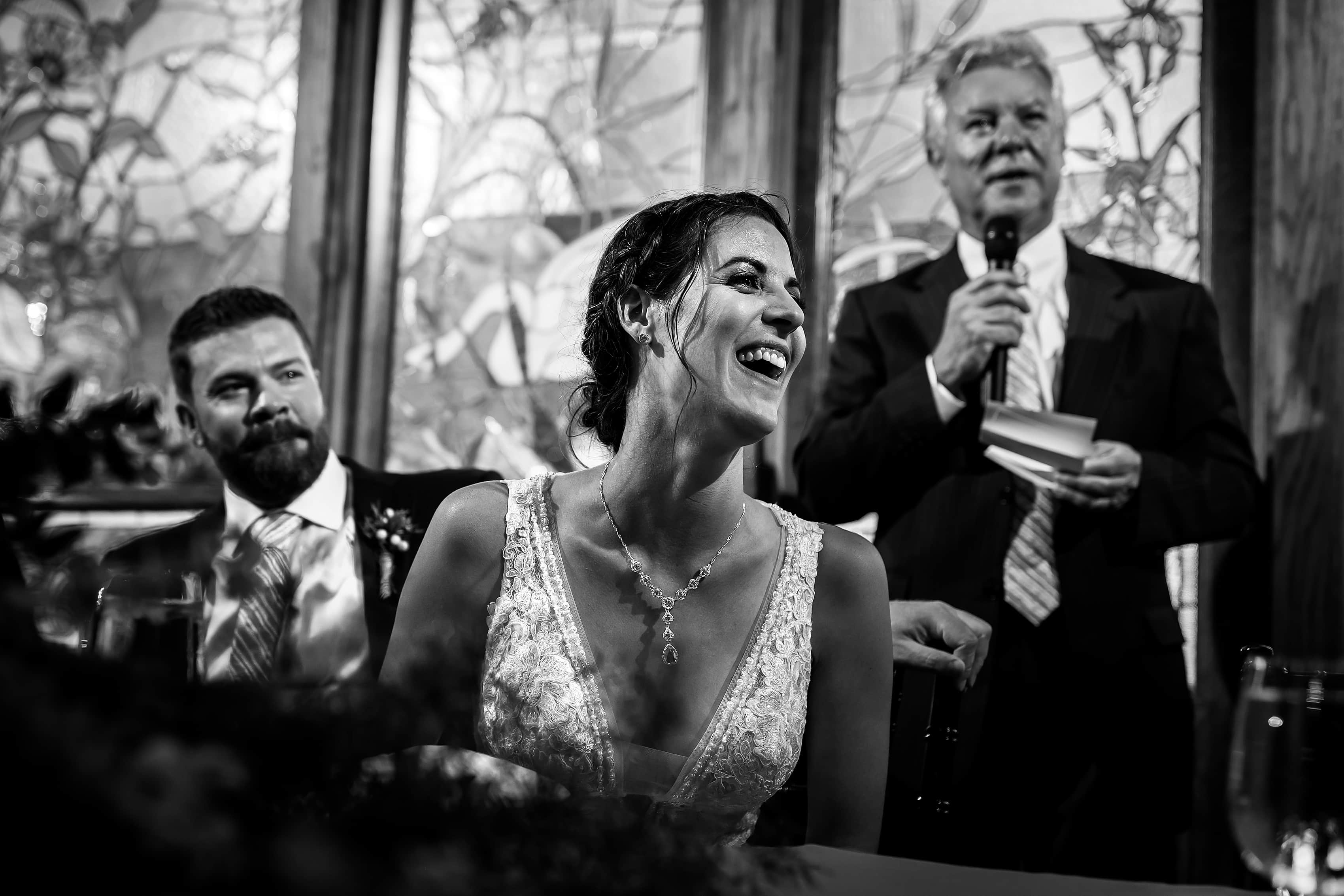 bride laughs during father of the bride toast during Lionsgate Event Center wedding reception
