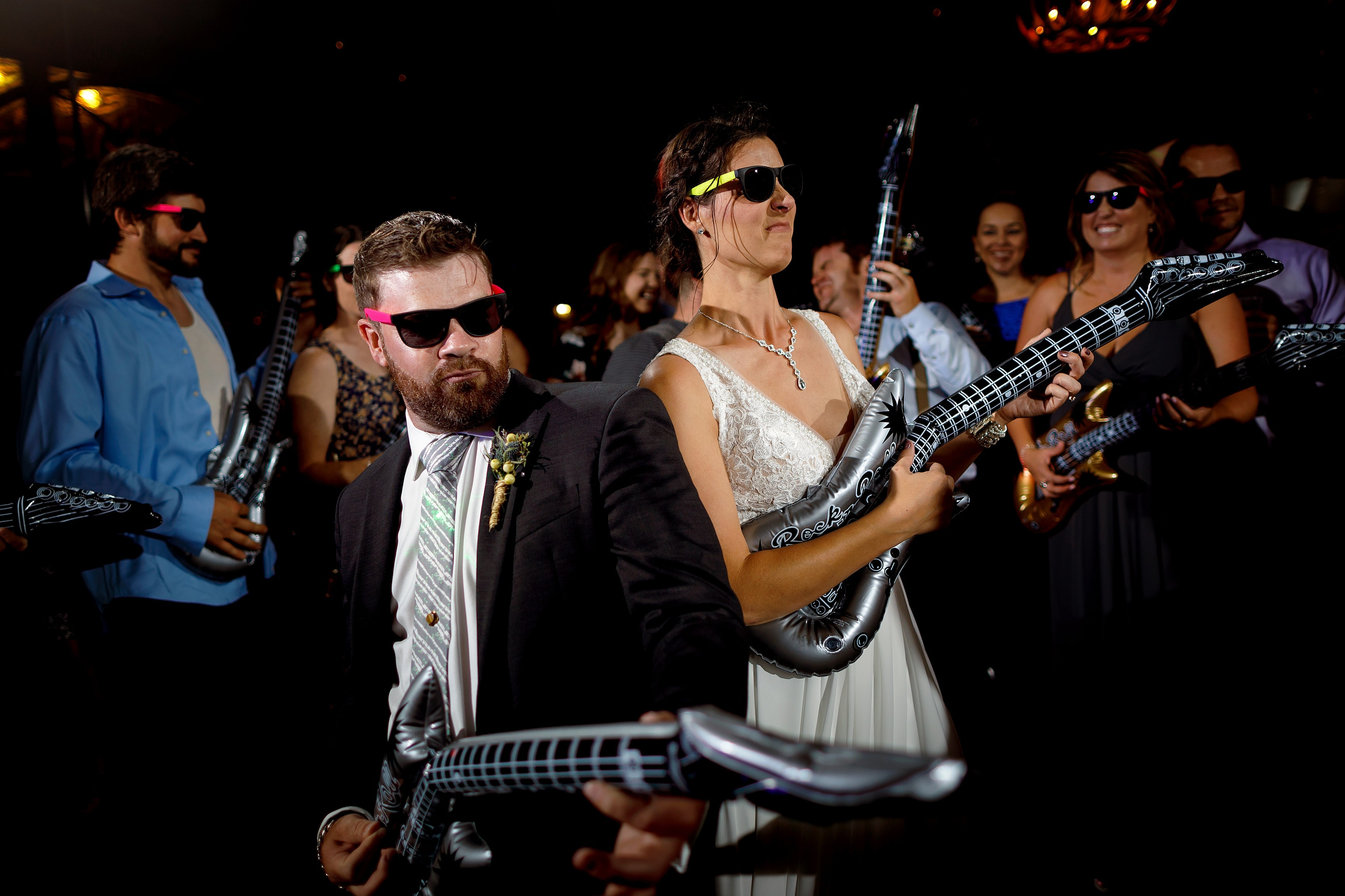 bride and groom play inflatable guitars during Lionsgate Event Center wedding reception