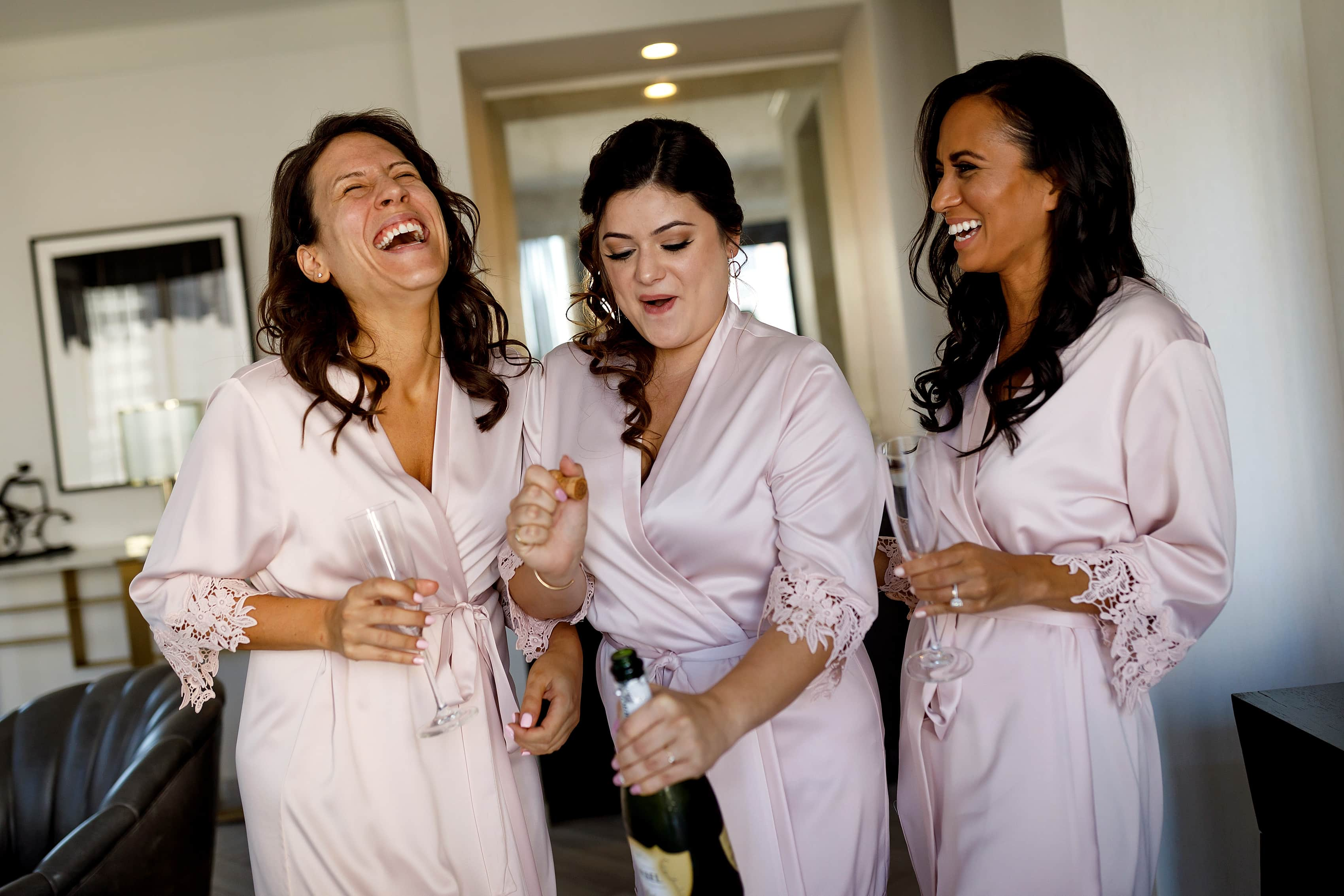 bridesmaids popping champagne in Lux Suite at Gwen Hotel in downtown Chicago