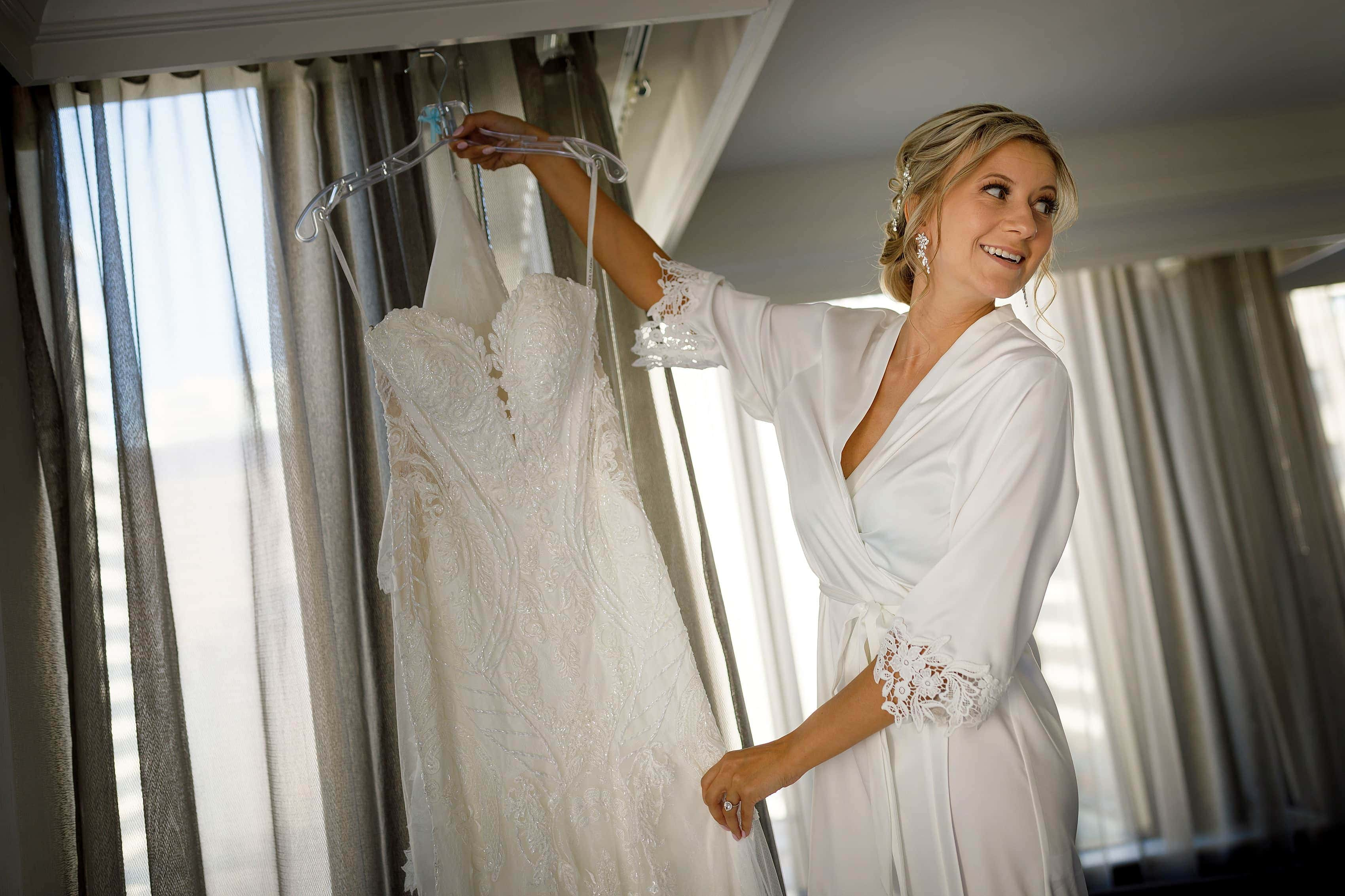 Bride taking dress down off hanger in Lux Suite at Gwen Hotel in downtown Chicago