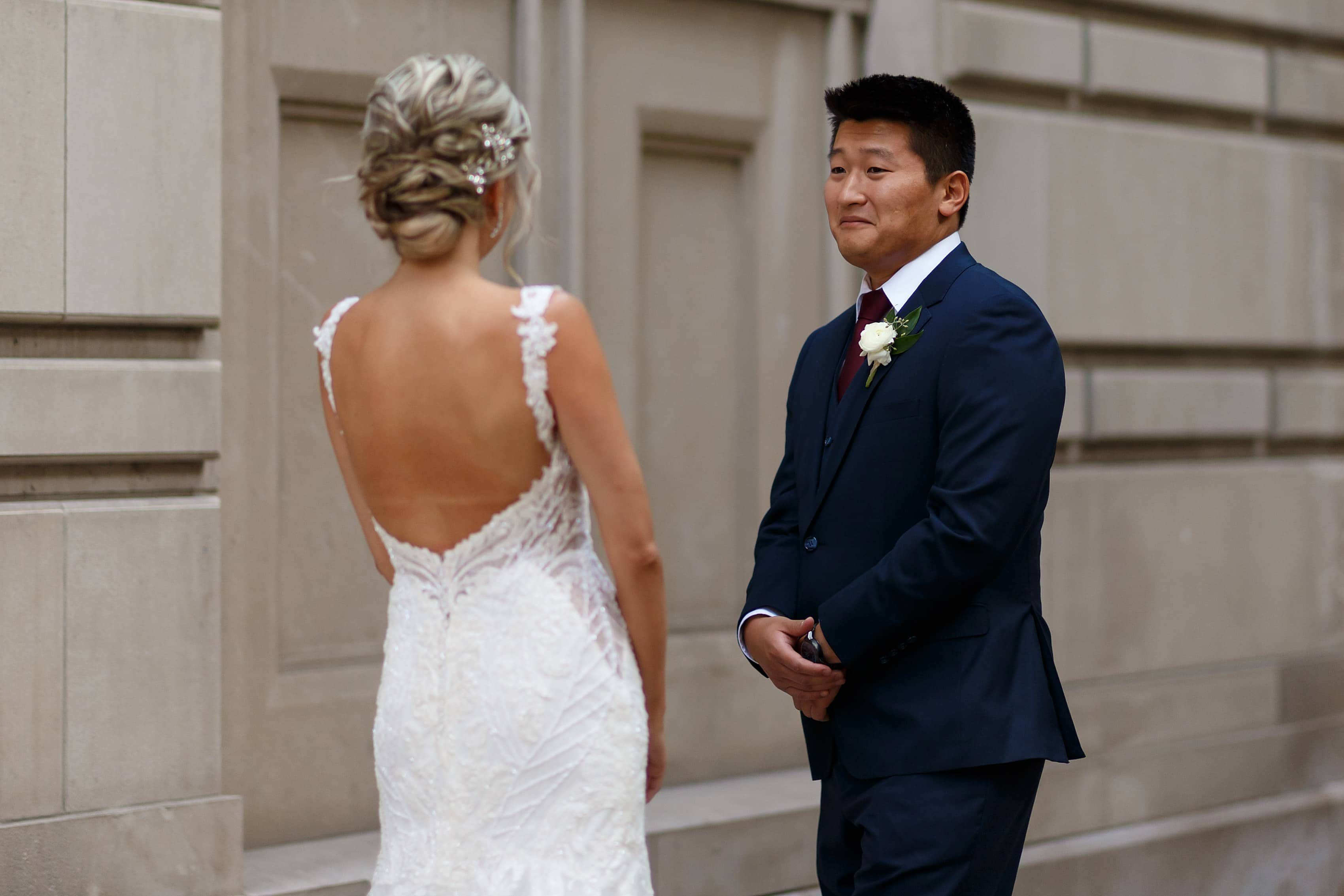 groom reacts to seeing bride during first look outside Wrigley Building in downtown Chicago