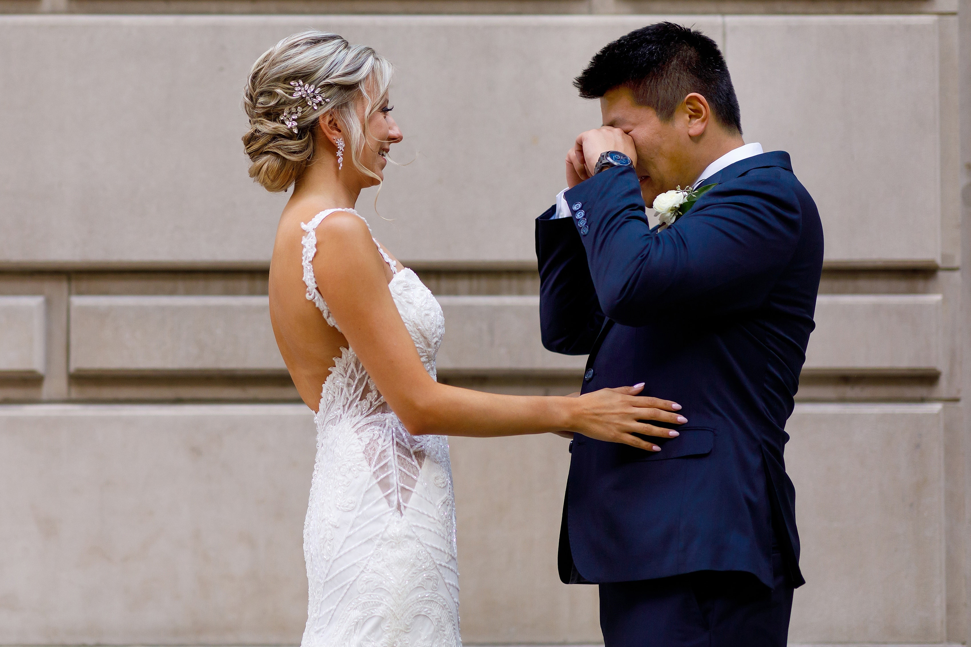 groom wipes away tears after seeing bride during first look outside Wrigley Building in downtown Chicago