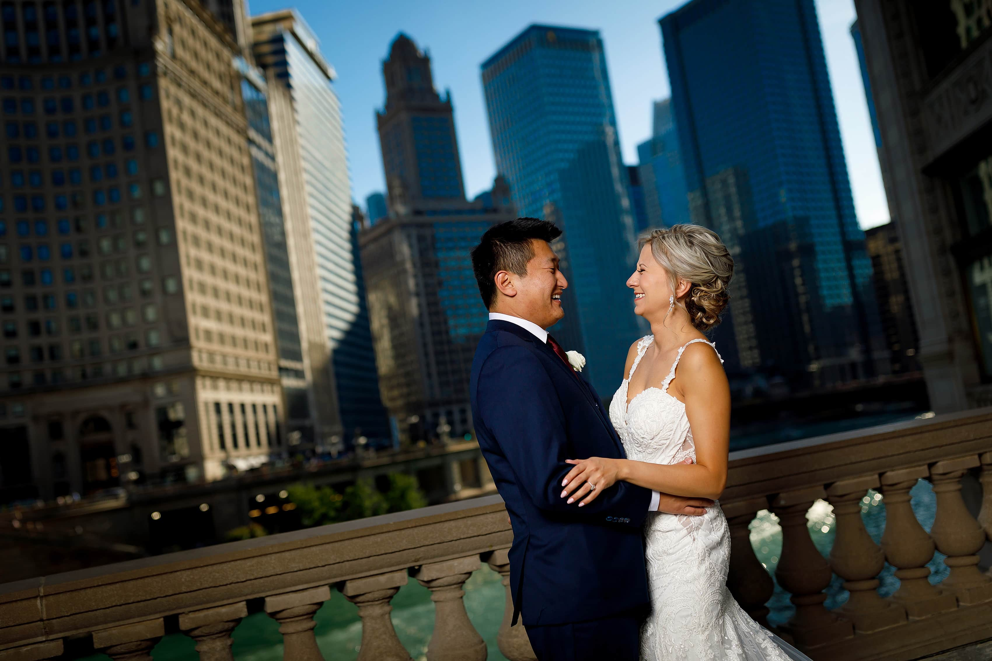 Bride and groom pose for a portrait outside the Wrigley Building overlooking the buildings on the Chicago River