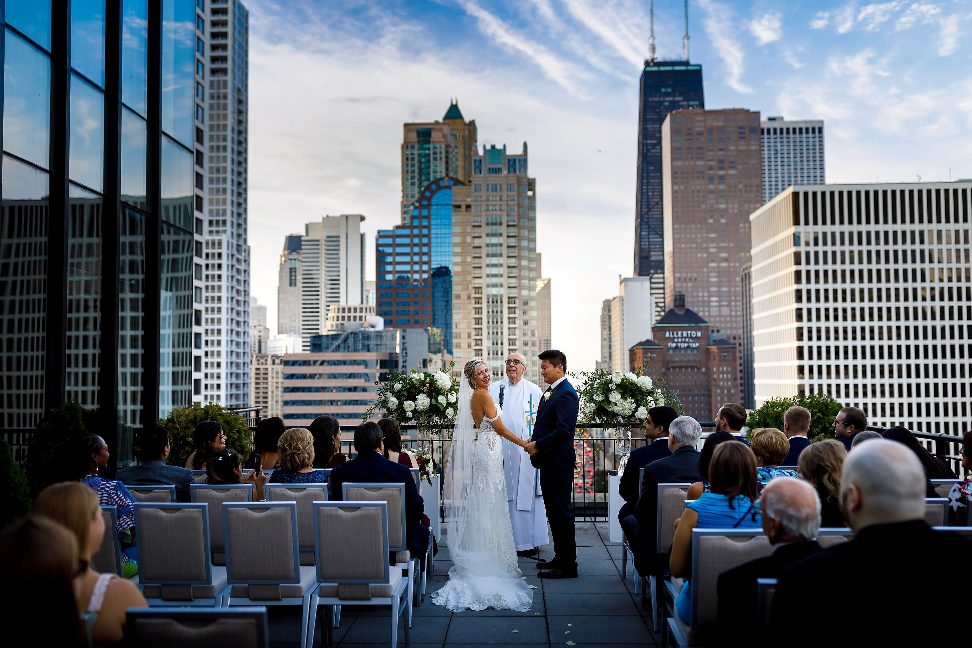 Bride laughs during wedding ceremony on the patio of the Lux Suite at The Gwen Hotel in downtown Chicago
