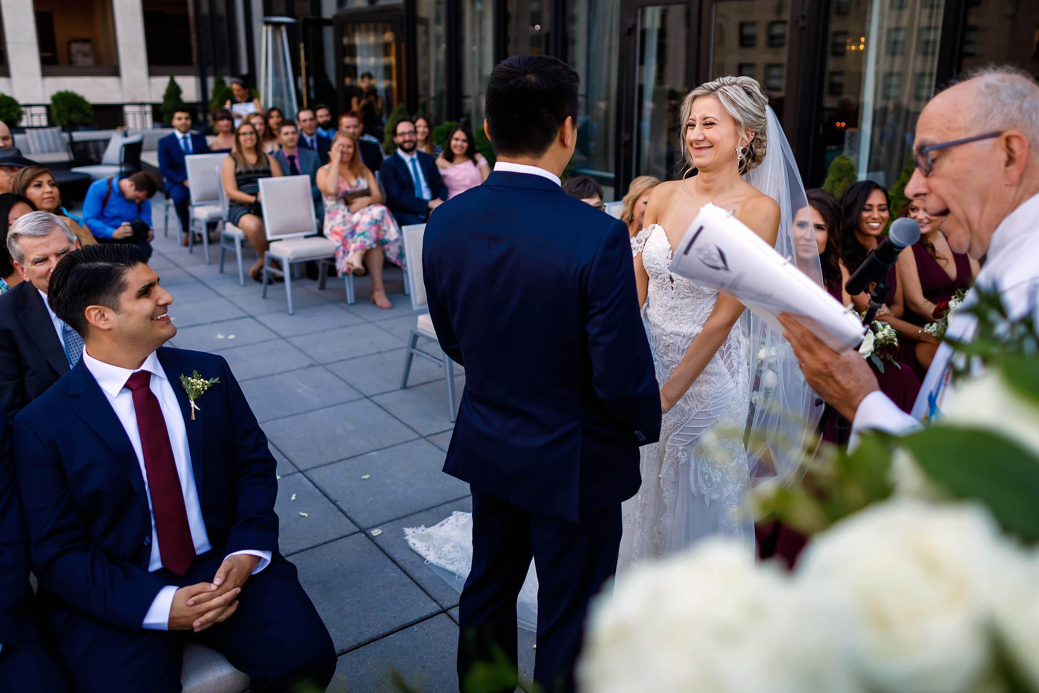 Bride and groom laugh during wedding ceremony on the patio of the Lux Suite at The Gwen Hotel in downtown Chicago