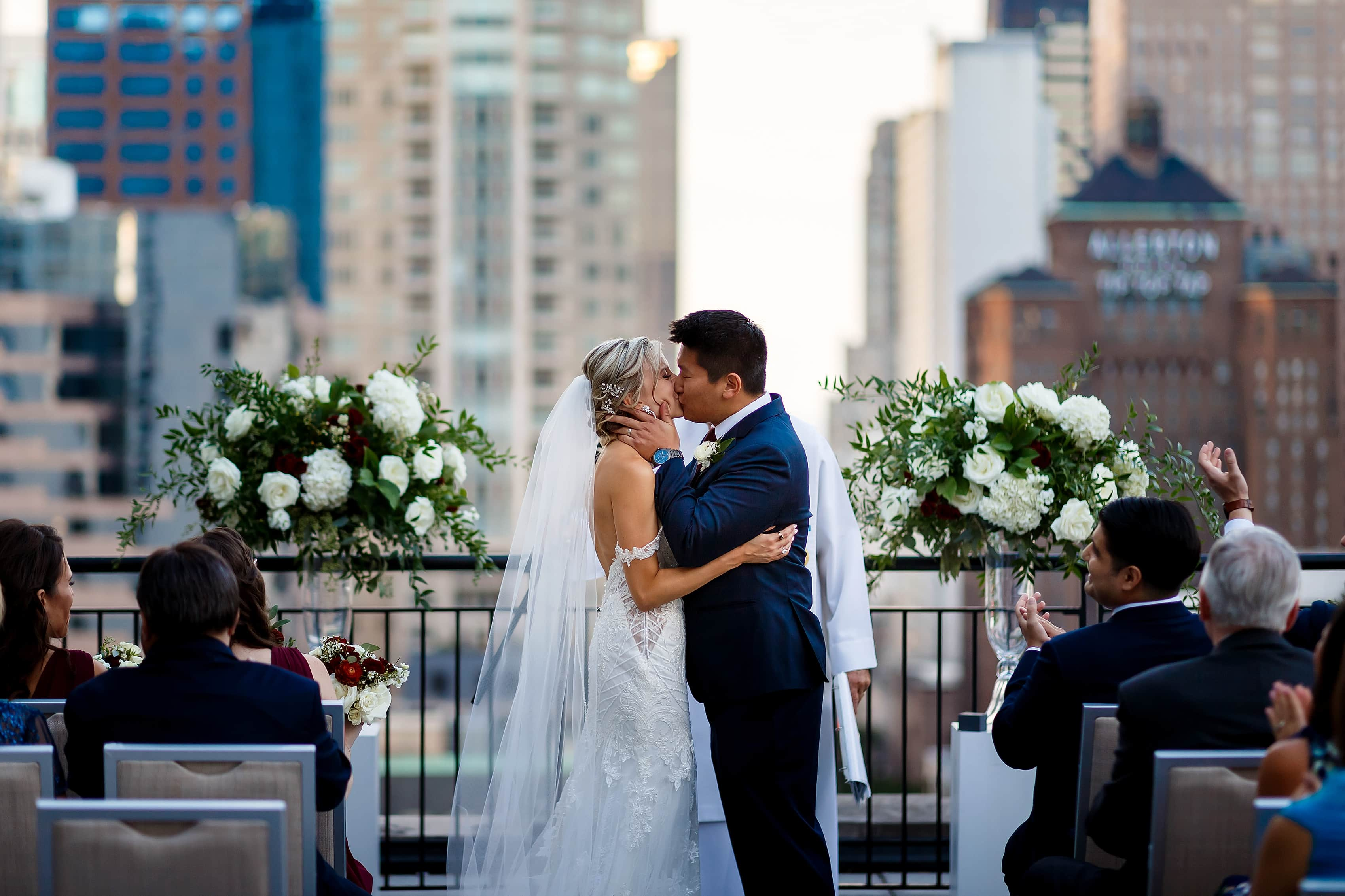 bride and groom kiss during wedding ceremony on the patio of the Lux Suite at The Gwen Hotel in downtown Chicago
