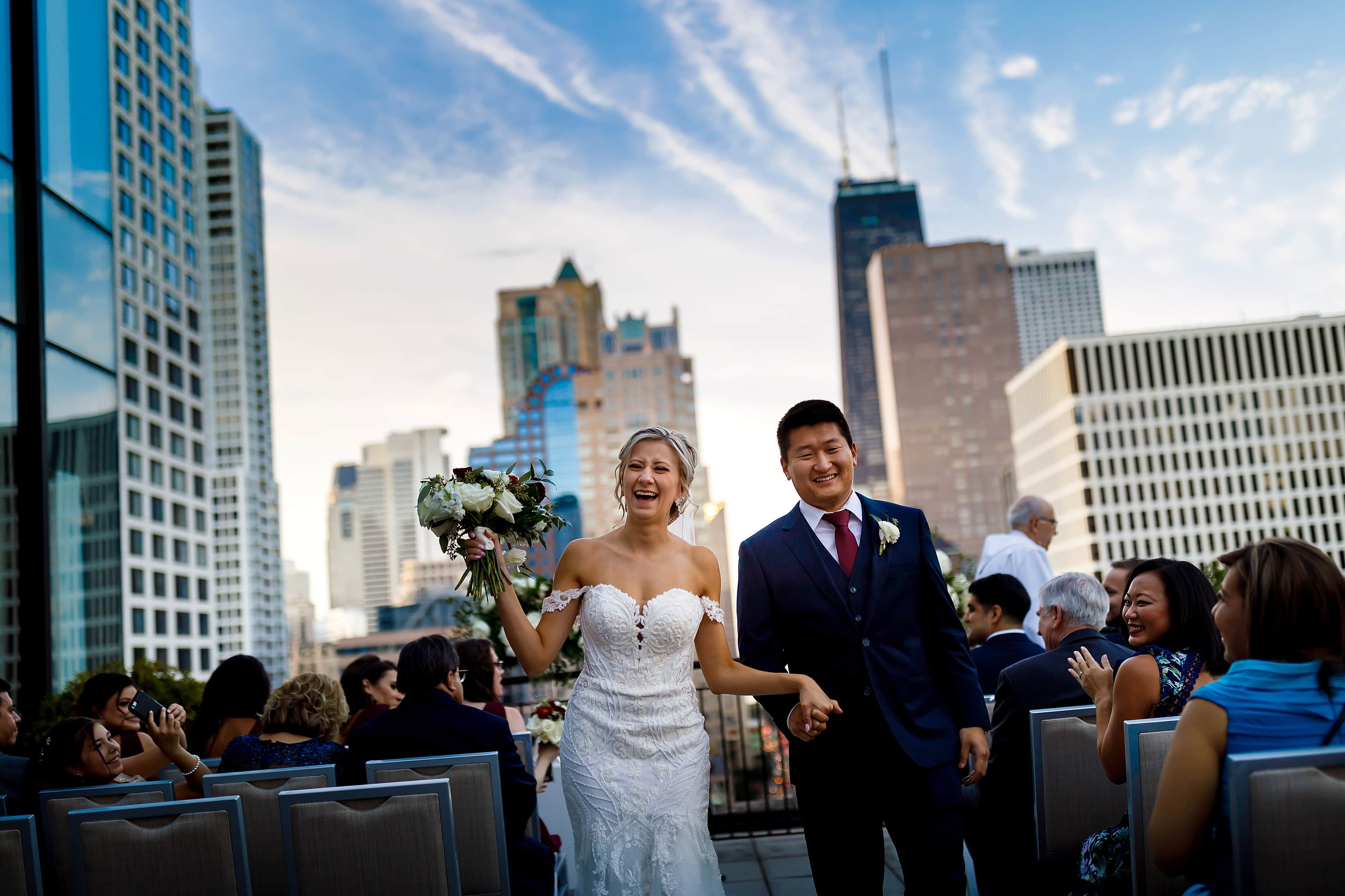 bride and groom walk back down the aisle after wedding ceremony on the patio of the Lux Suite at The Gwen Hotel in downtown Chicago