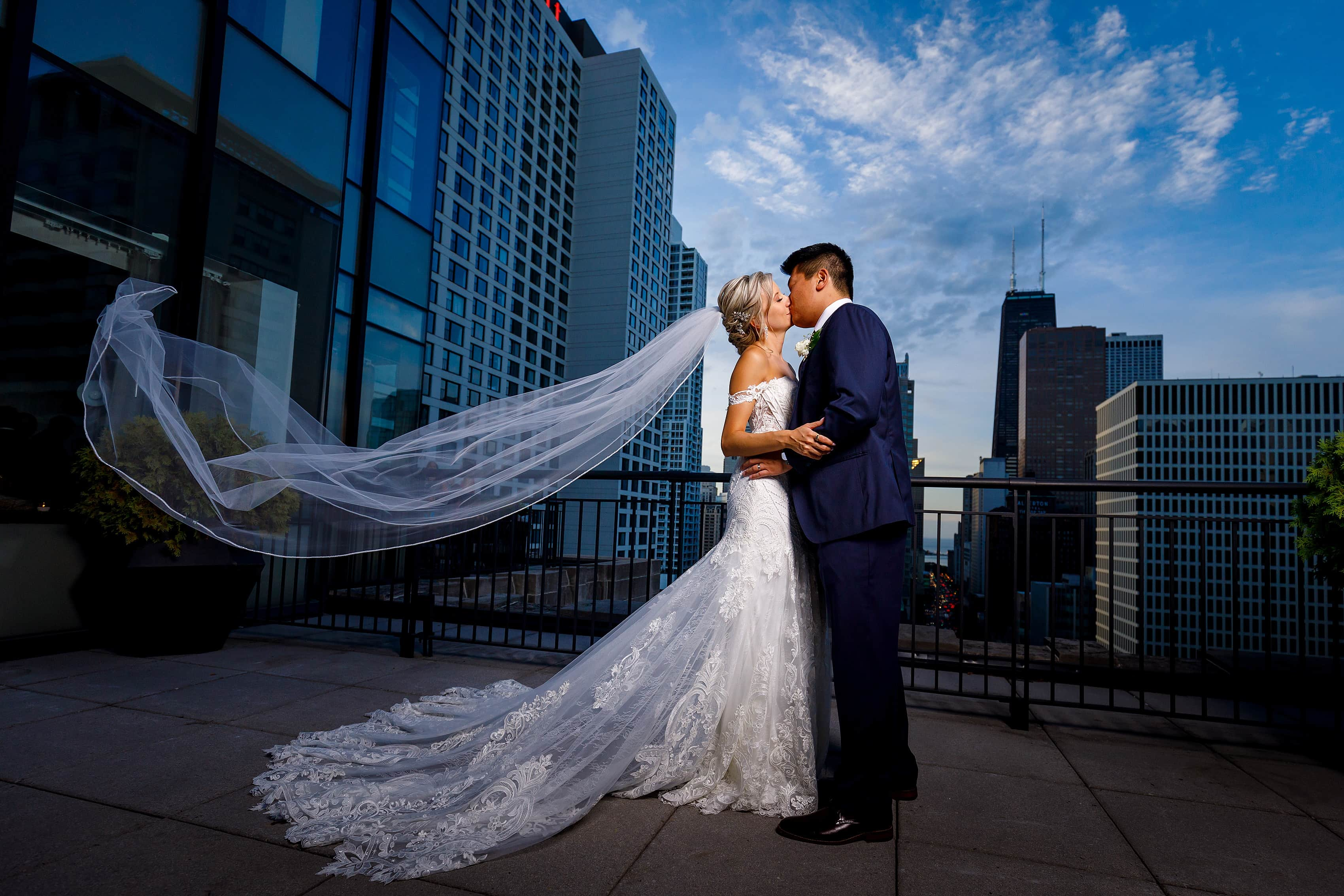 bride and groom pose for a portrait with blowing veil on the patio of the Lux Suite at The Gwen Hotel in downtown Chicago