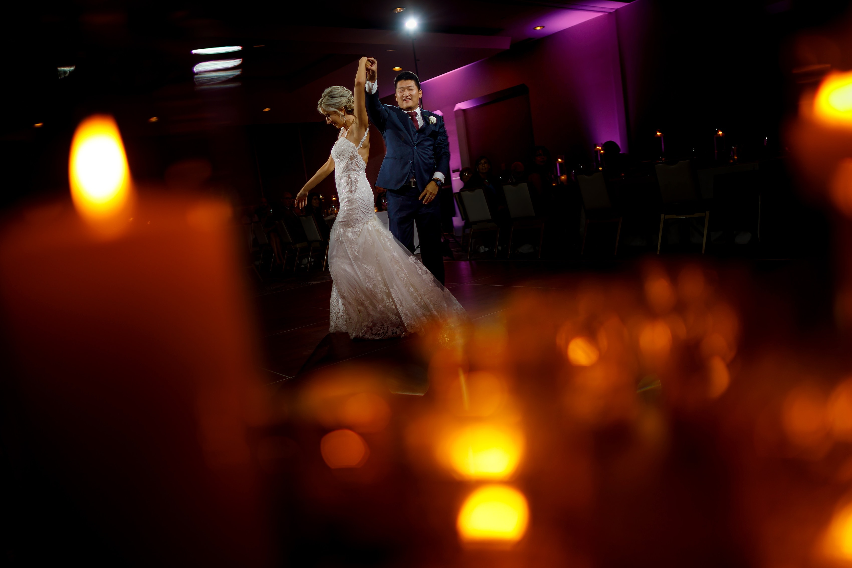 Bride and groom share first dance with purple uplighting and candle bokeh during wedding reception The Gwen Hotel in downtown Chicago