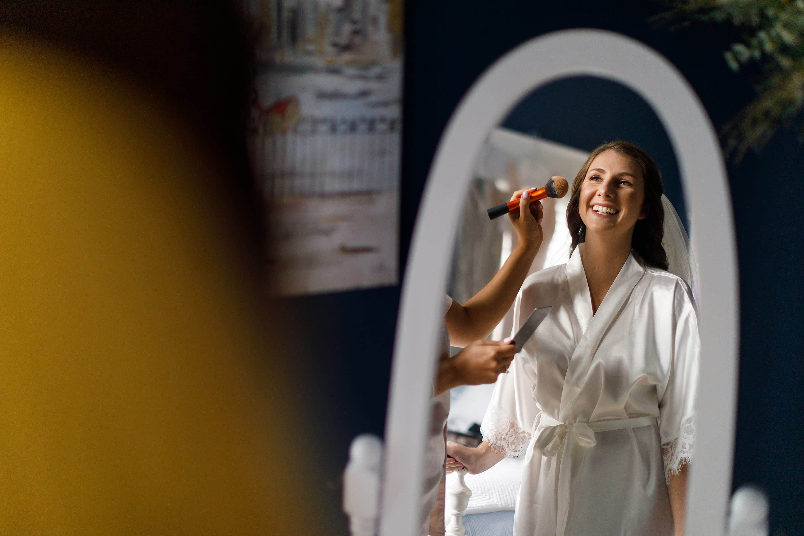 Bride has her makeup done while looking in mirror getting ready for wedding