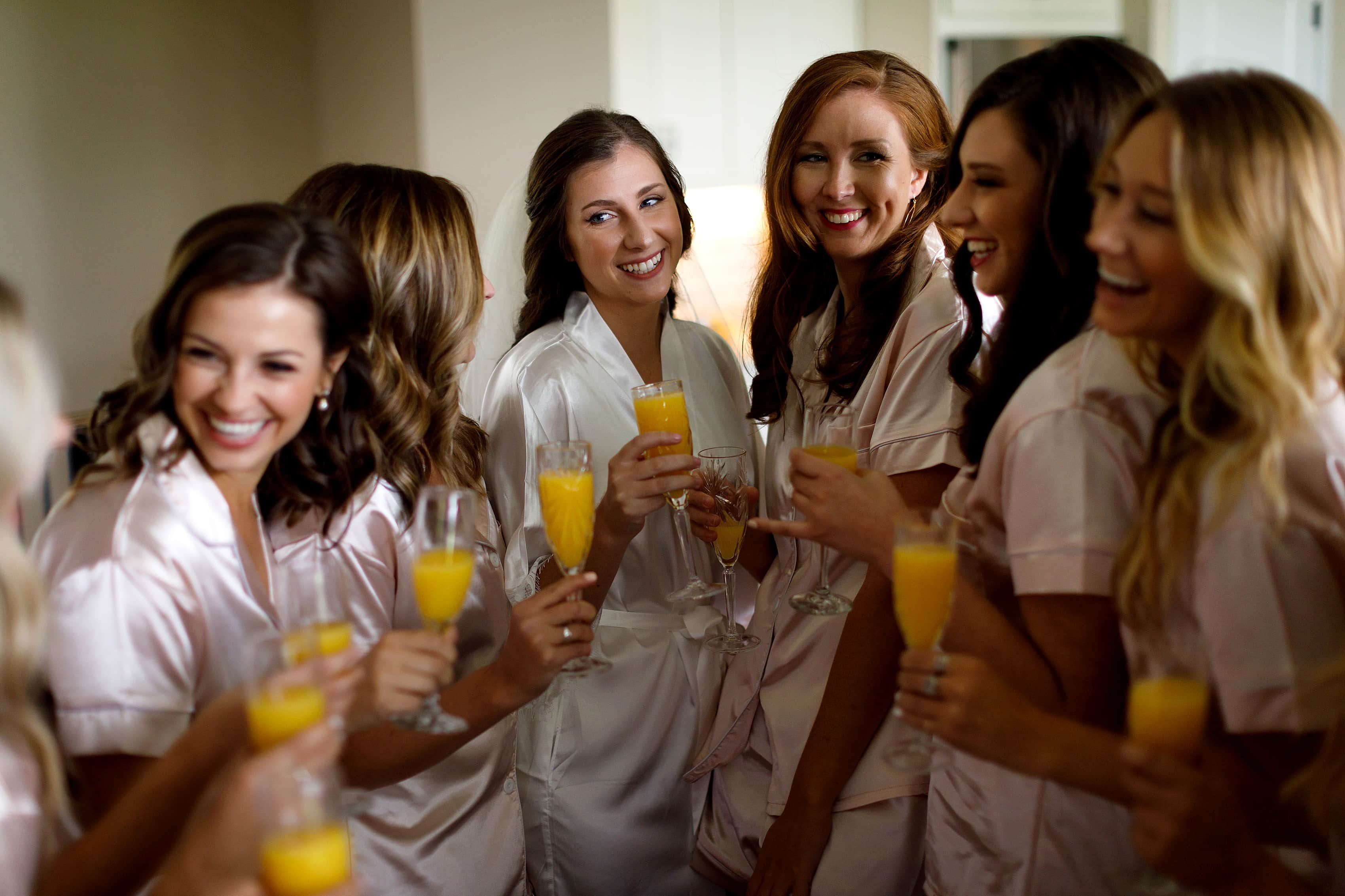 Bride cheers with bridesmaids toast while getting ready for her wedding