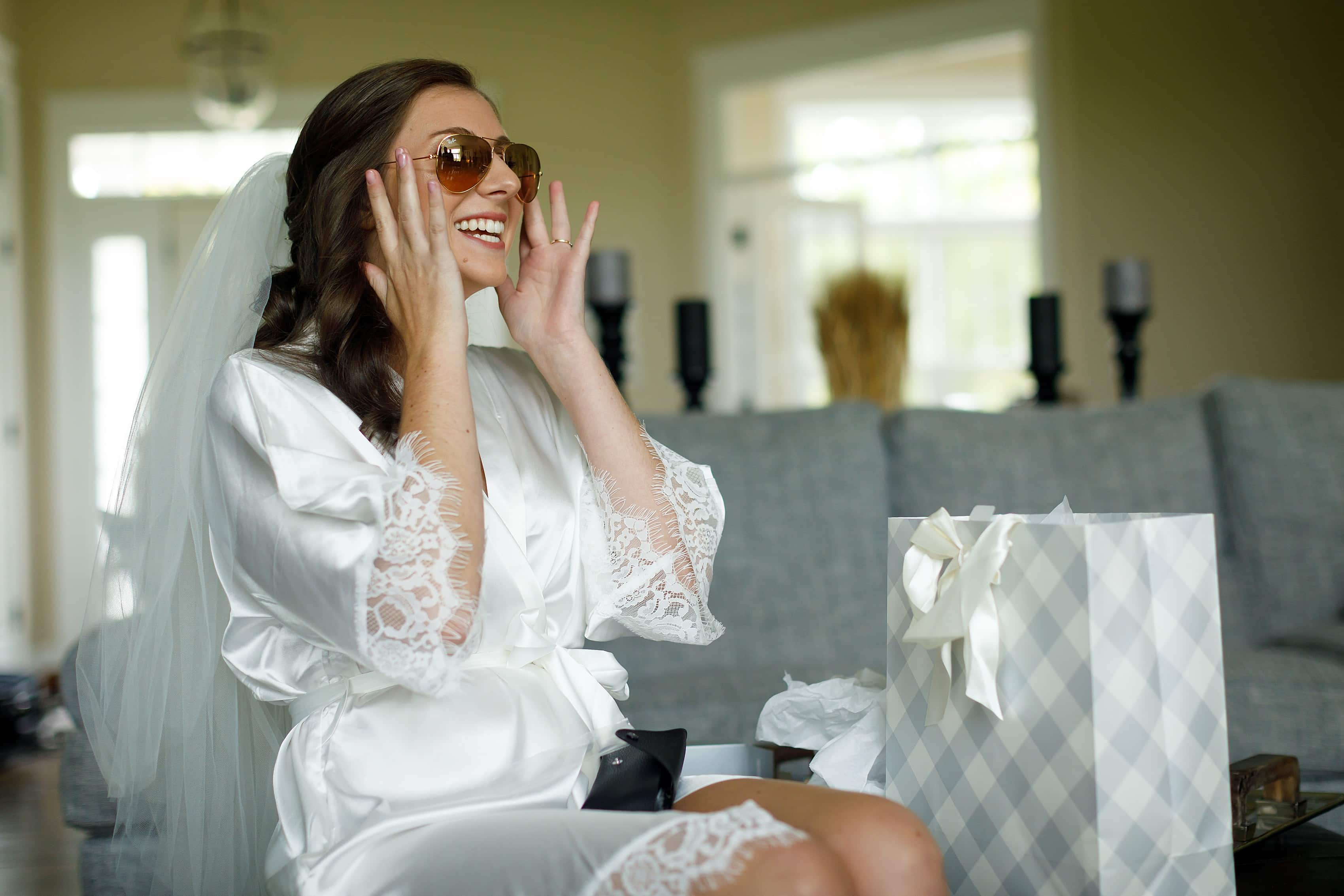 Bride tries on sunglasses while getting ready for wedding