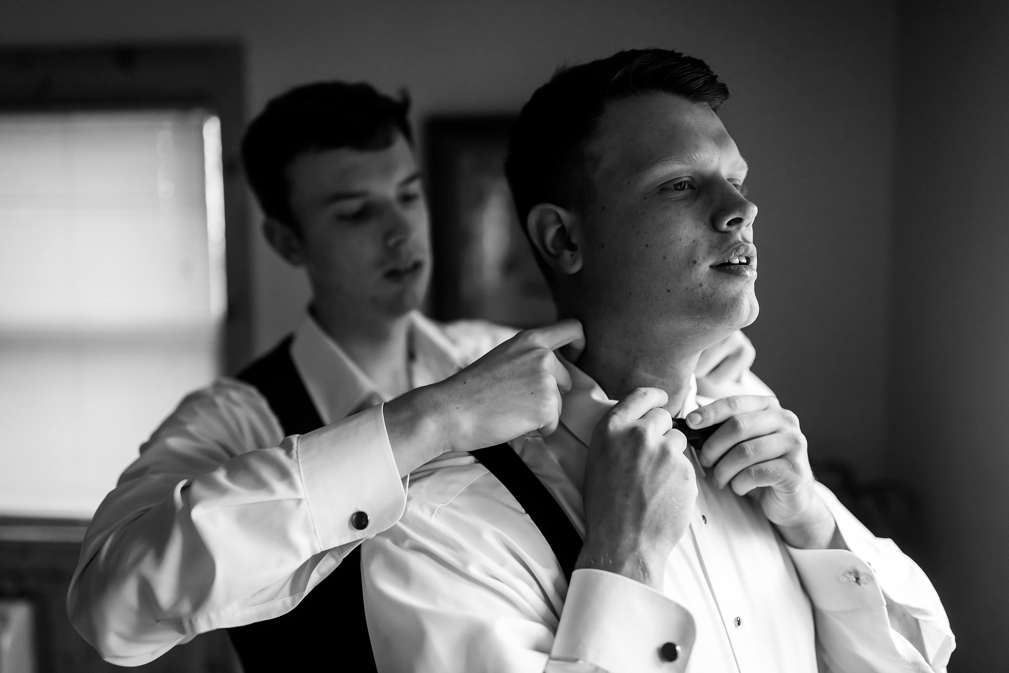 Best man helps groom with tie while getting ready for wedding
