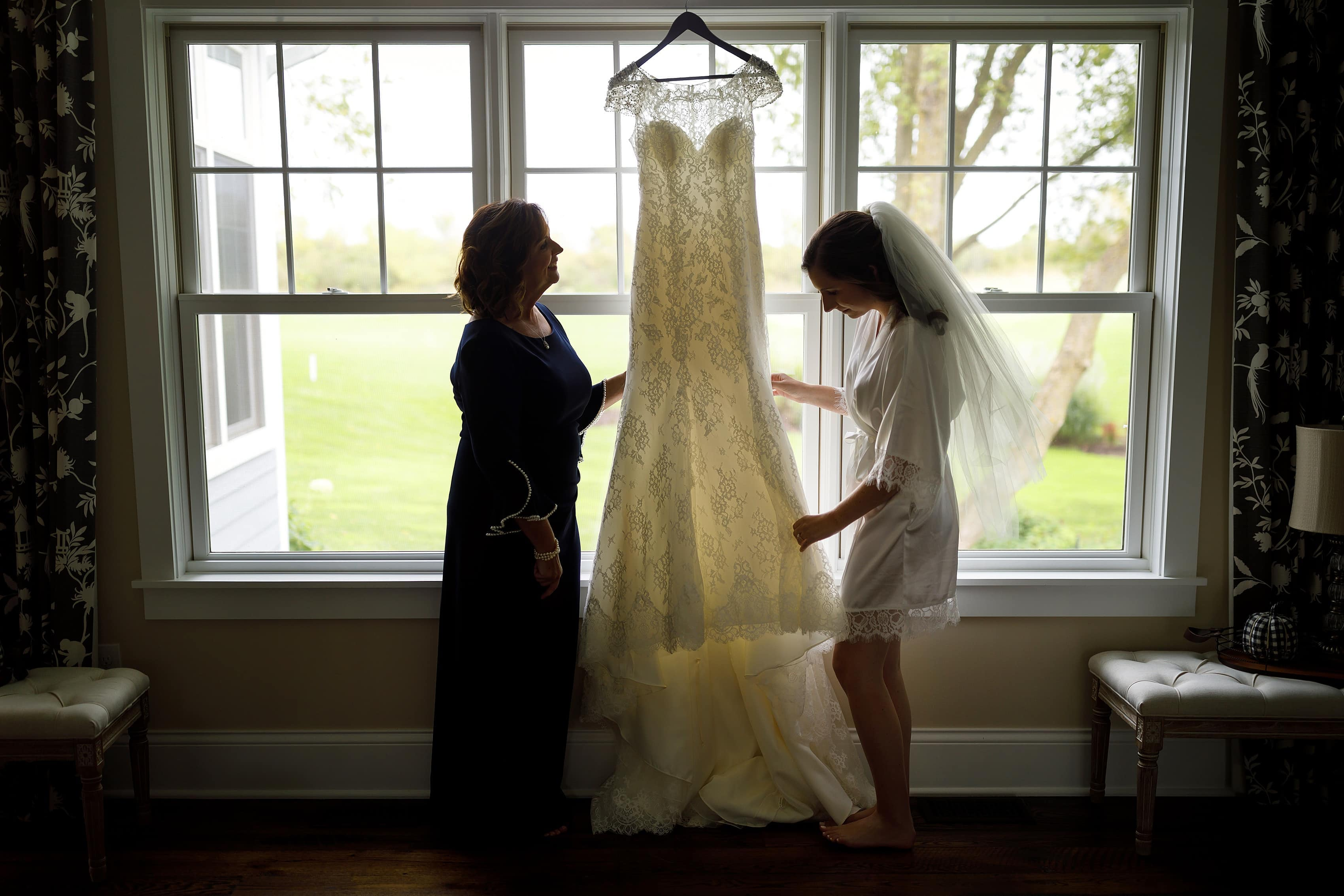 Bride and mom look at wedding dress while getting ready for wedding