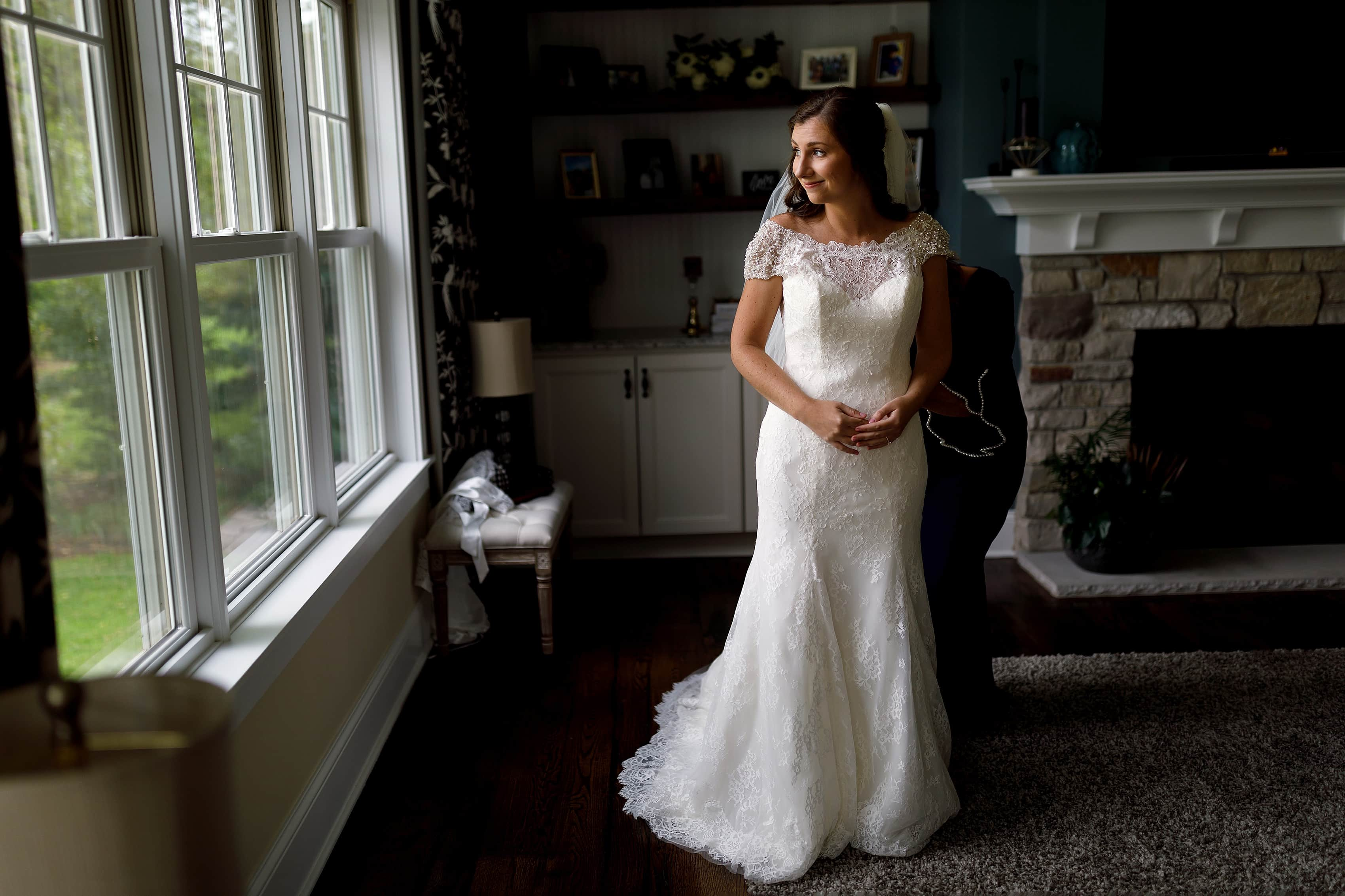 Bride gets into dress with her mom while getting ready for wedding