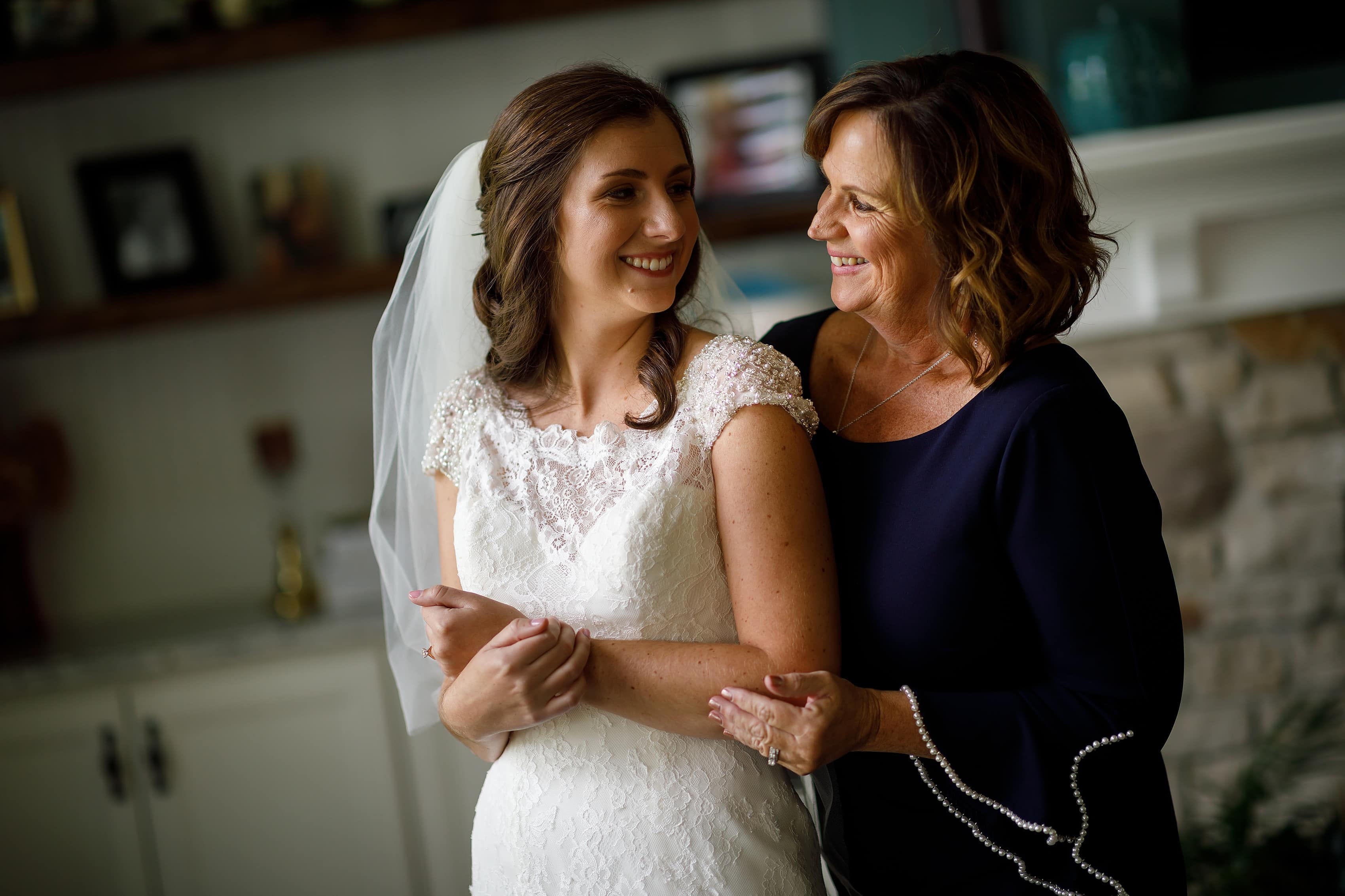 Mother hugs her daughter the bride while getting ready for wedding