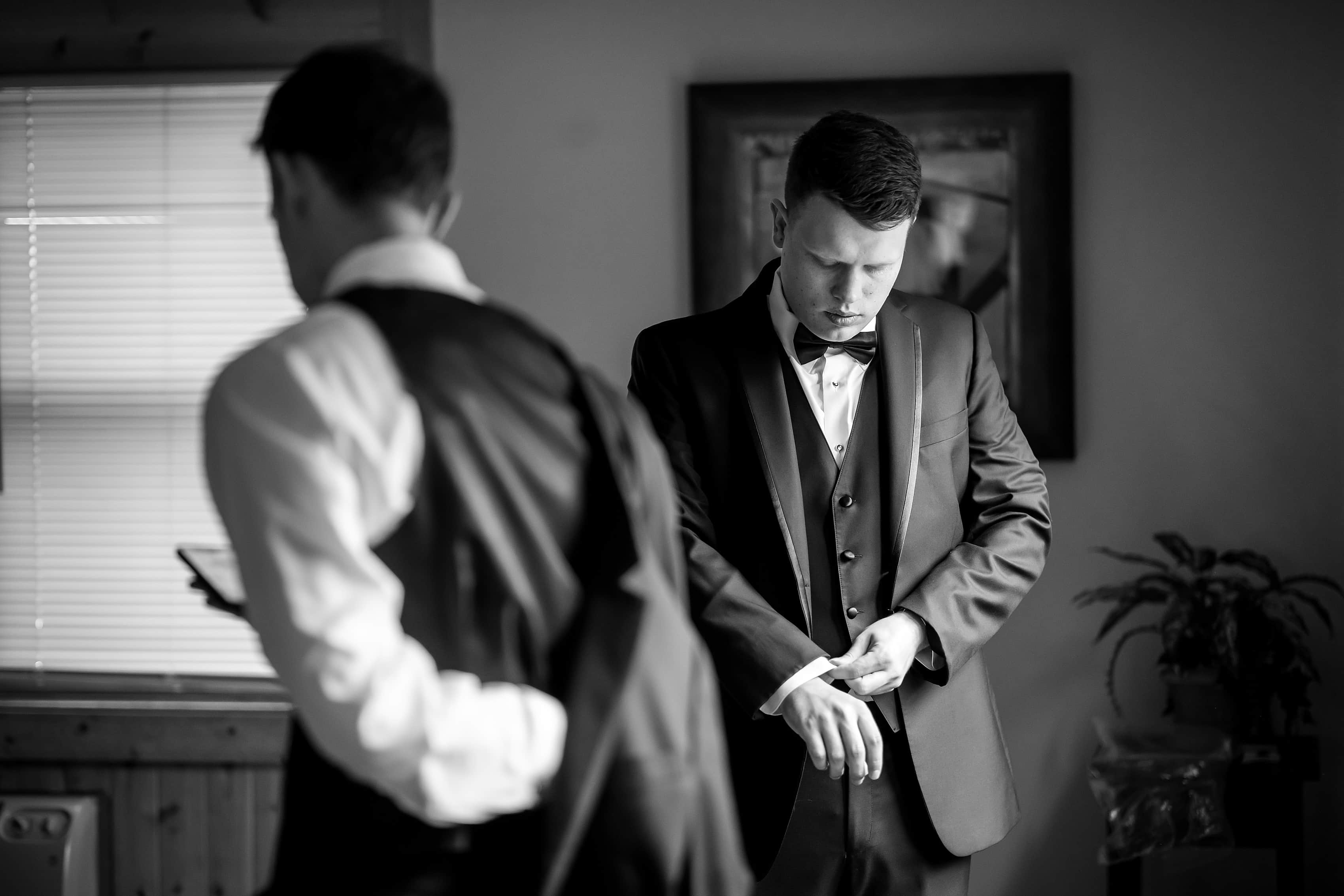 Groom puts on shirt and jacket while getting ready for wedding