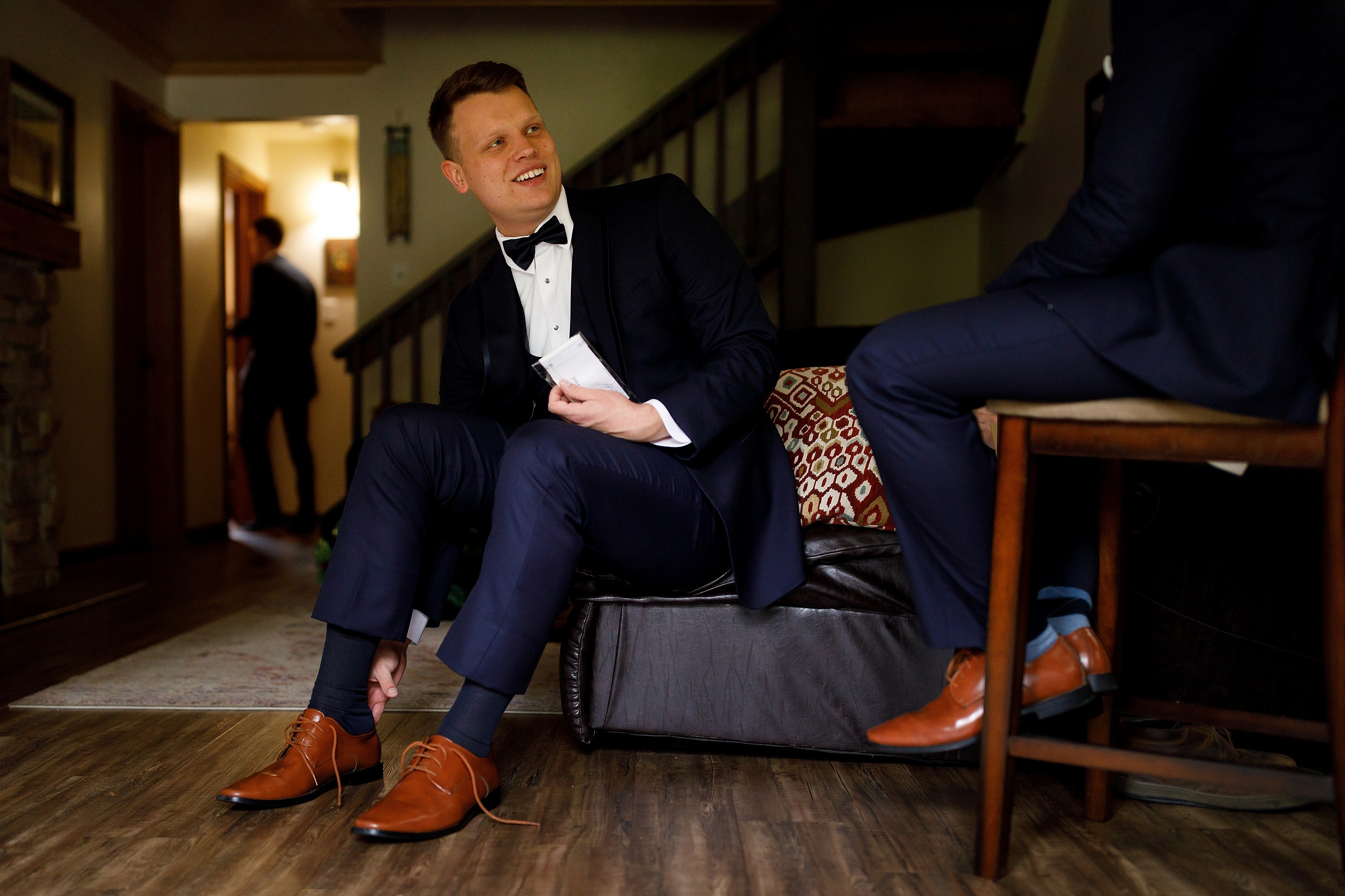 Groom puts on shoes while getting ready for wedding