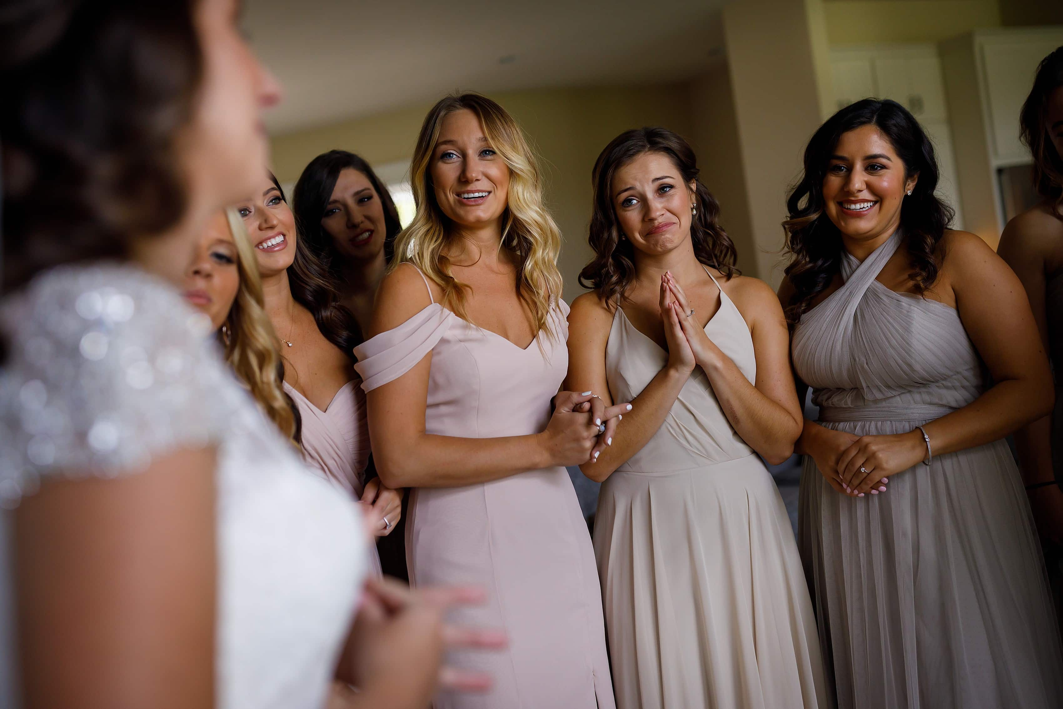 Group of bridesmaids reacts to seeing bride in her dress while getting ready for wedding