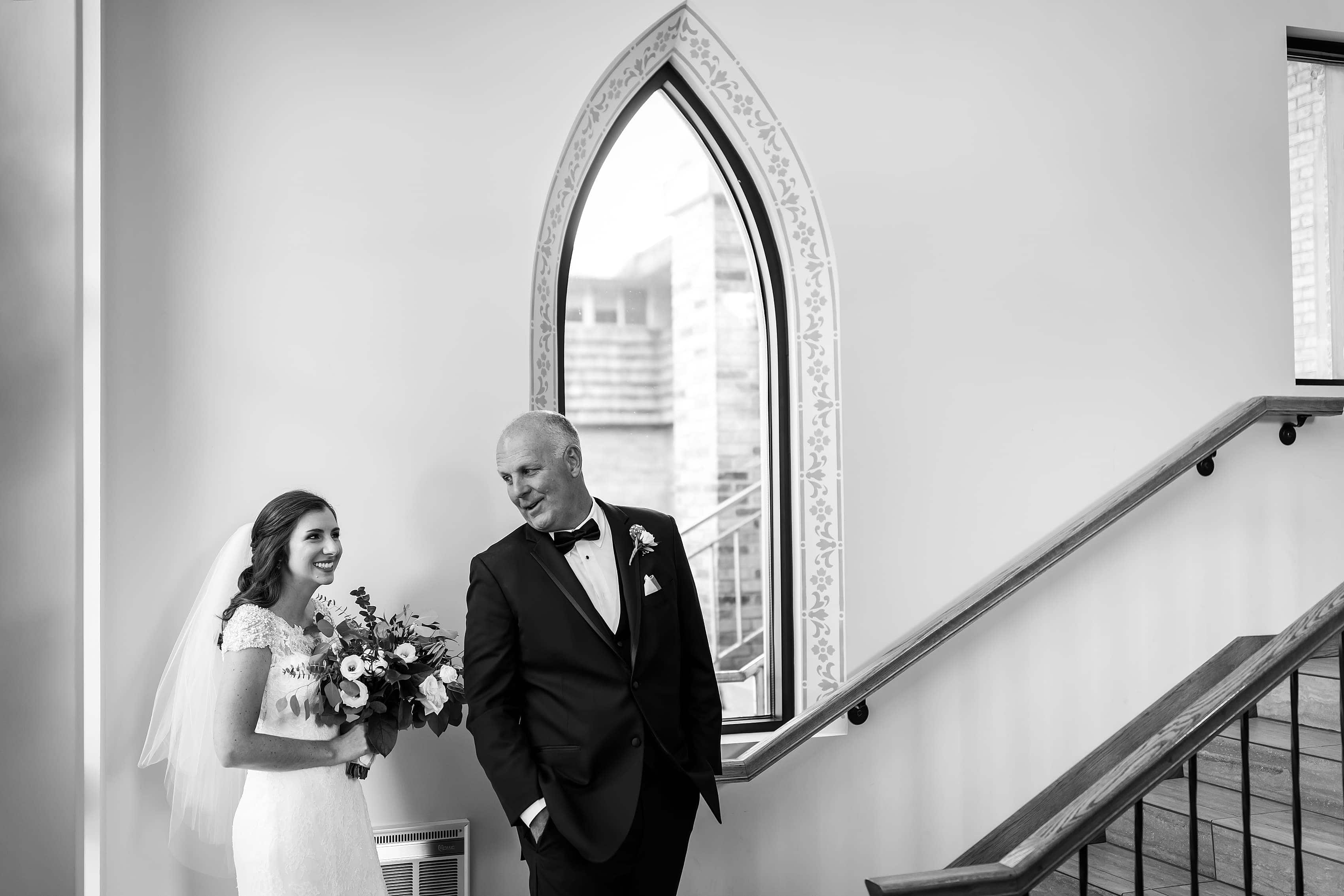 Father of the bride and daughter get ready outside church to walk down the aisle