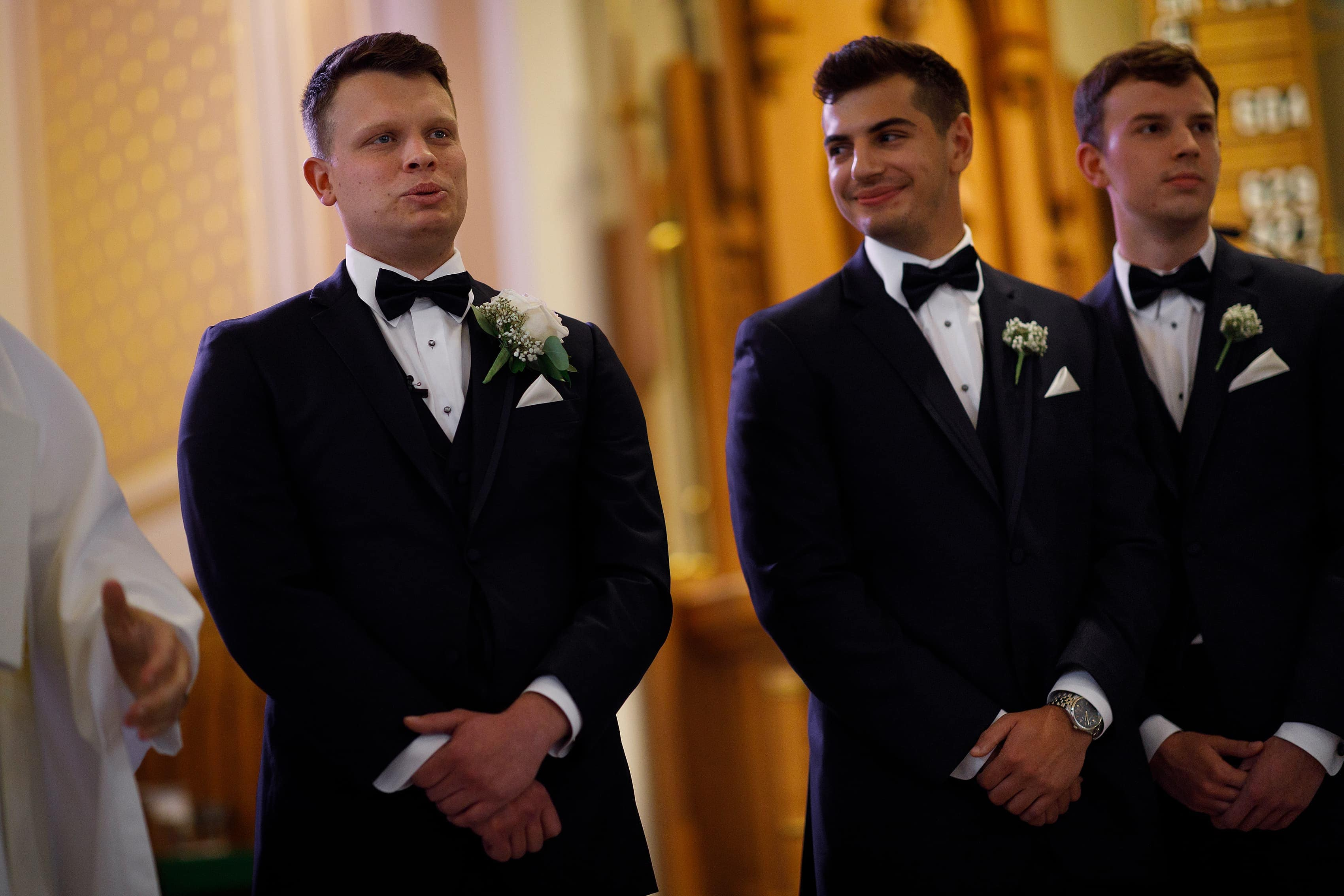 Groom reacts to seeing bride as she walks down the aisle at St. Francis Church in Lake Geneva, Wisconsin