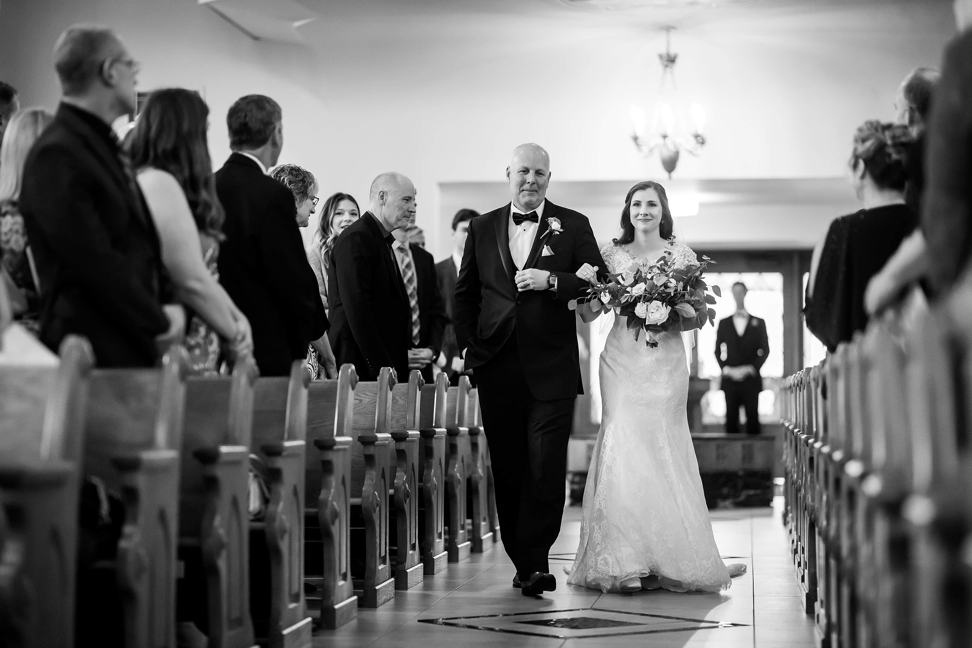 Bride walks down the aisle with her dad at St. Francis Church in Lake Geneva, Wisconsin