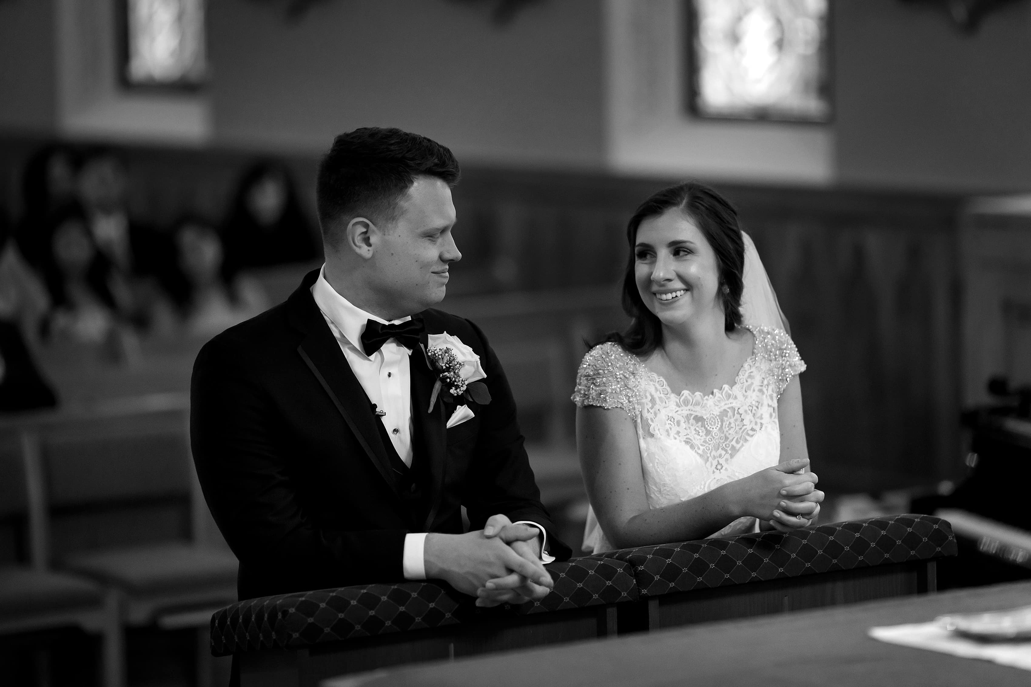 Bride and groom smile at the alter during wedding ceremony at St. Francis Church in Lake Geneva, Wisconsin