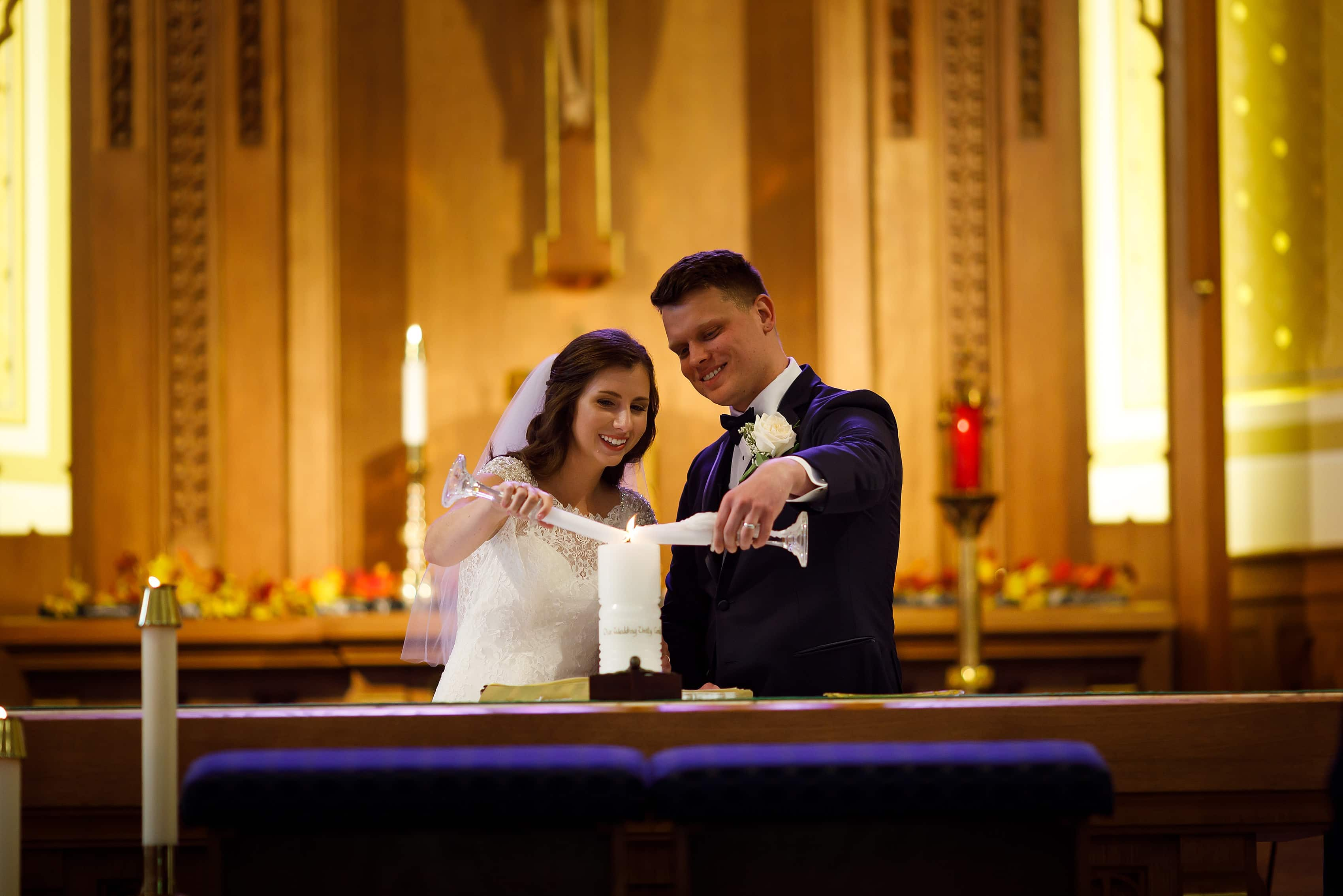Bride and groom light the unity candle at the alter during wedding ceremony at St. Francis Church in Lake Geneva, Wisconsin