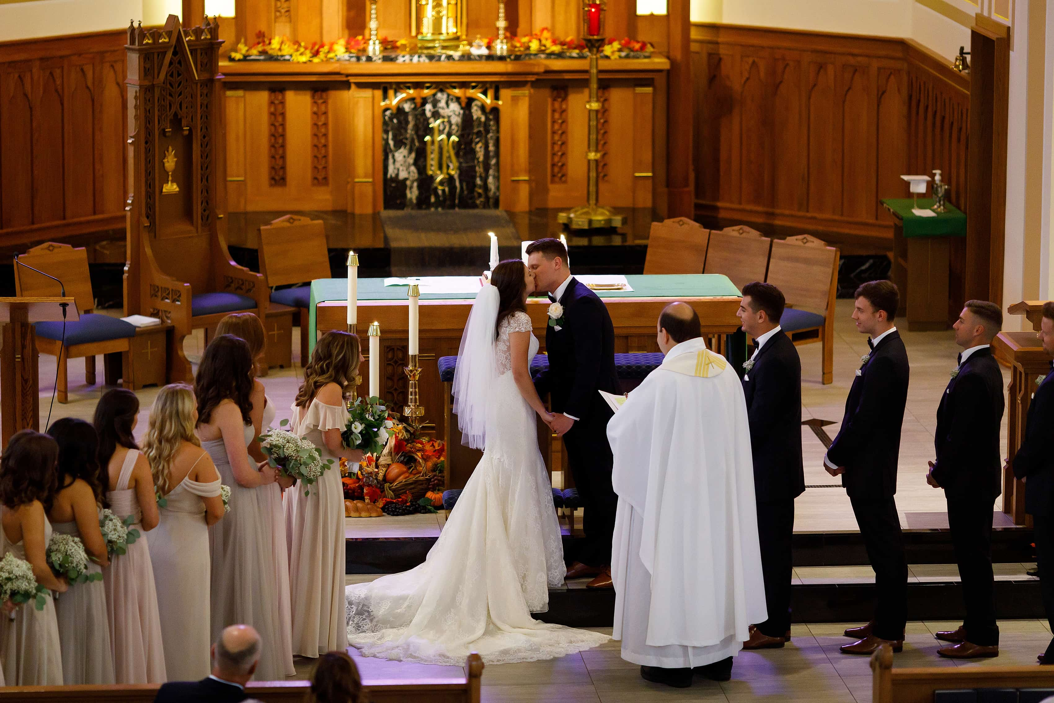 Bride and groom share first kiss at the alter during wedding ceremony at St. Francis Church in Lake Geneva, Wisconsin