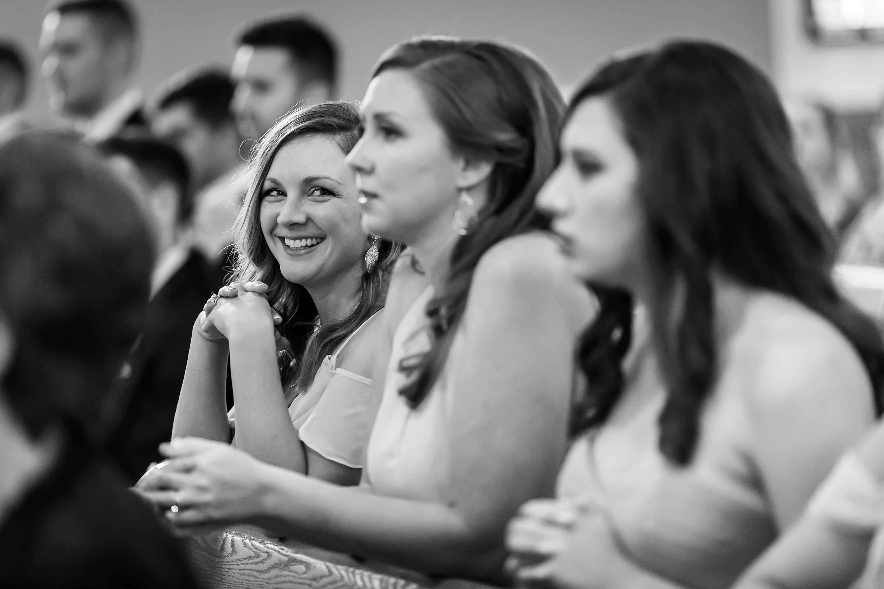 Bridesmaid smiles during wedding ceremony at St. Francis Church in Lake Geneva, Wisconsin