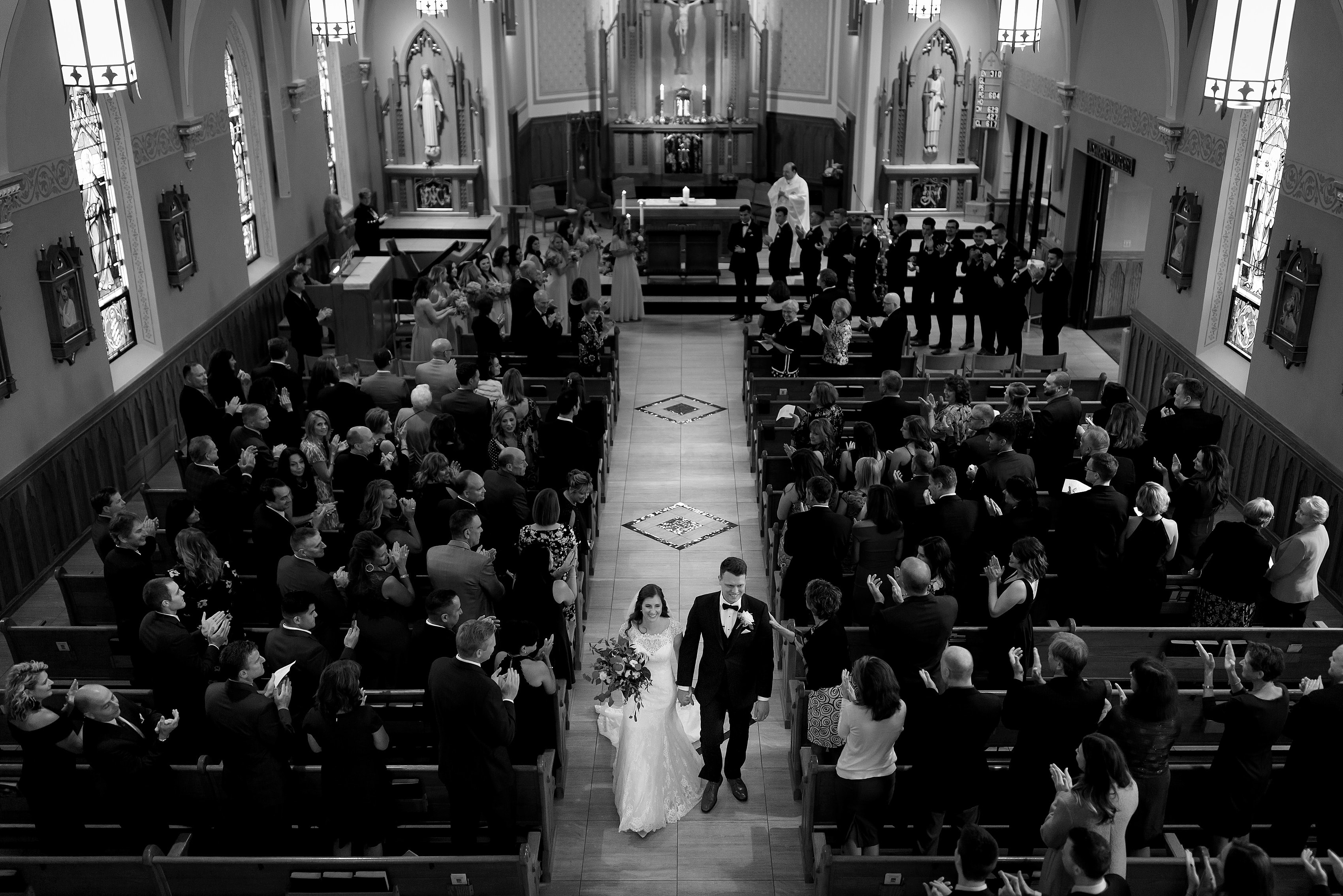 Bride and groom walk back down the aisle after wedding ceremony at St. Francis Church in Lake Geneva, Wisconsin