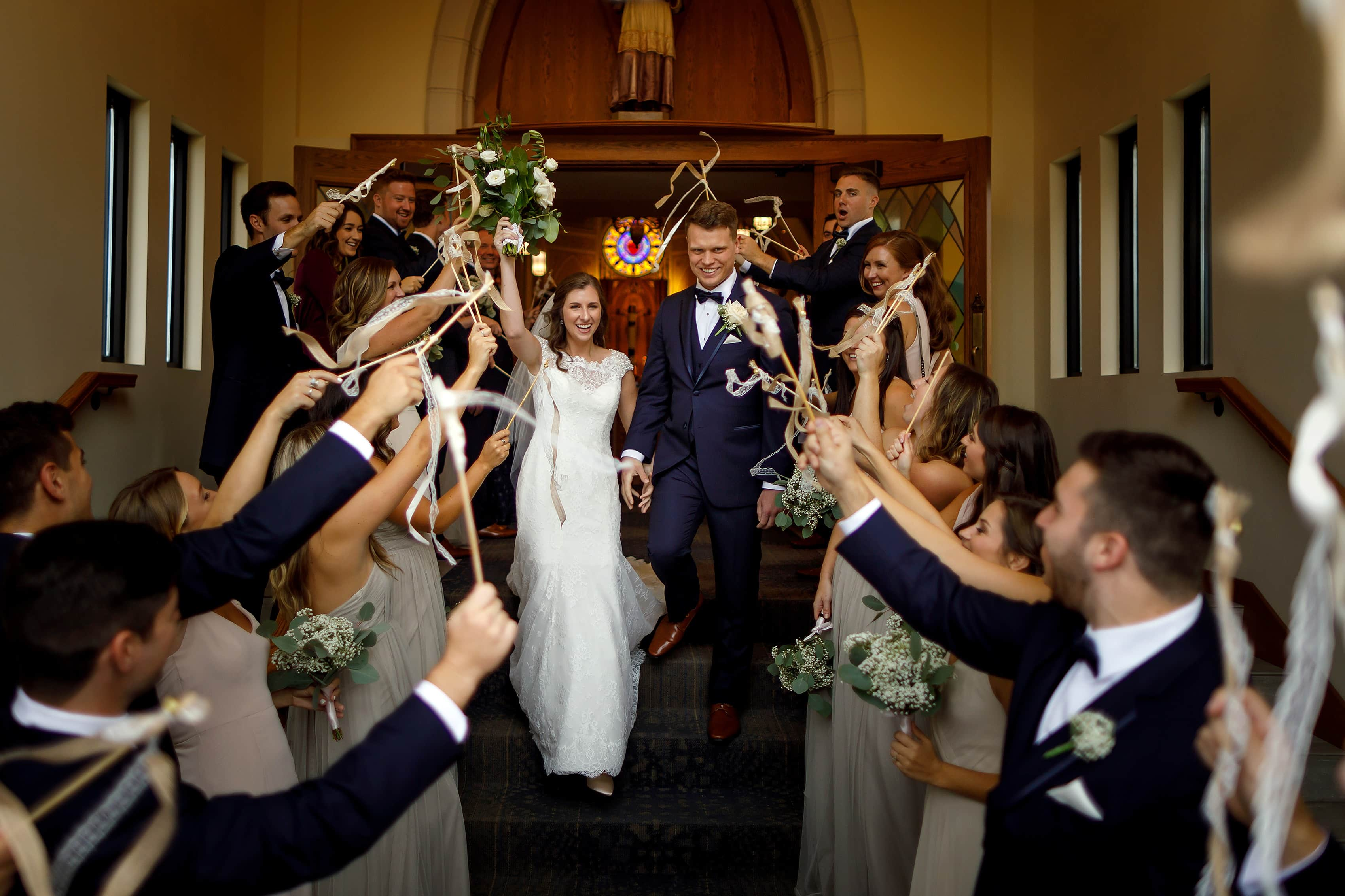 Bride and groom walk out to cheering wedding party after ceremony at St. Francis Church in Lake Geneva, Wisconsin