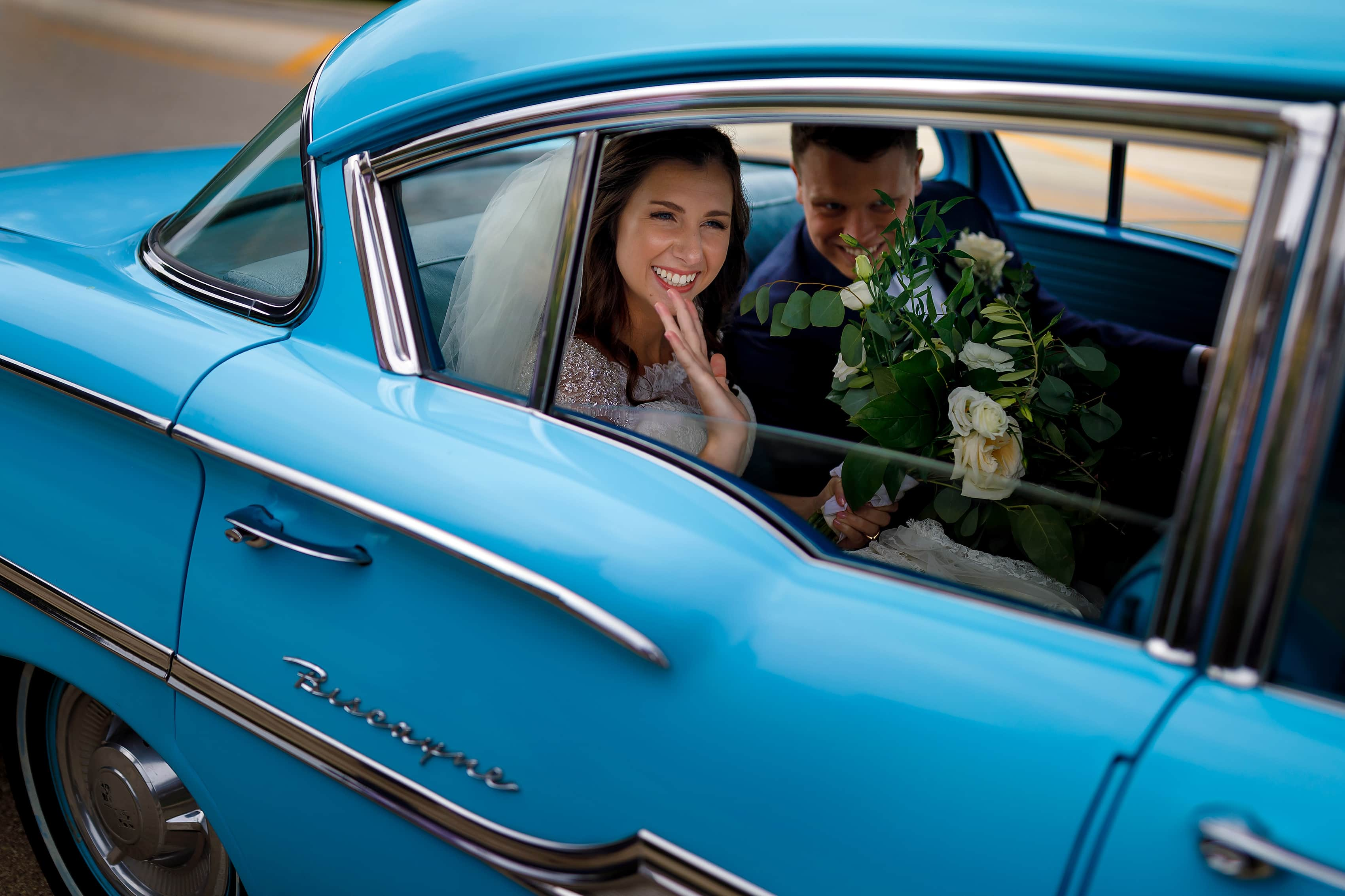 Bride and groom wave to guests while exiting wedding ceremony