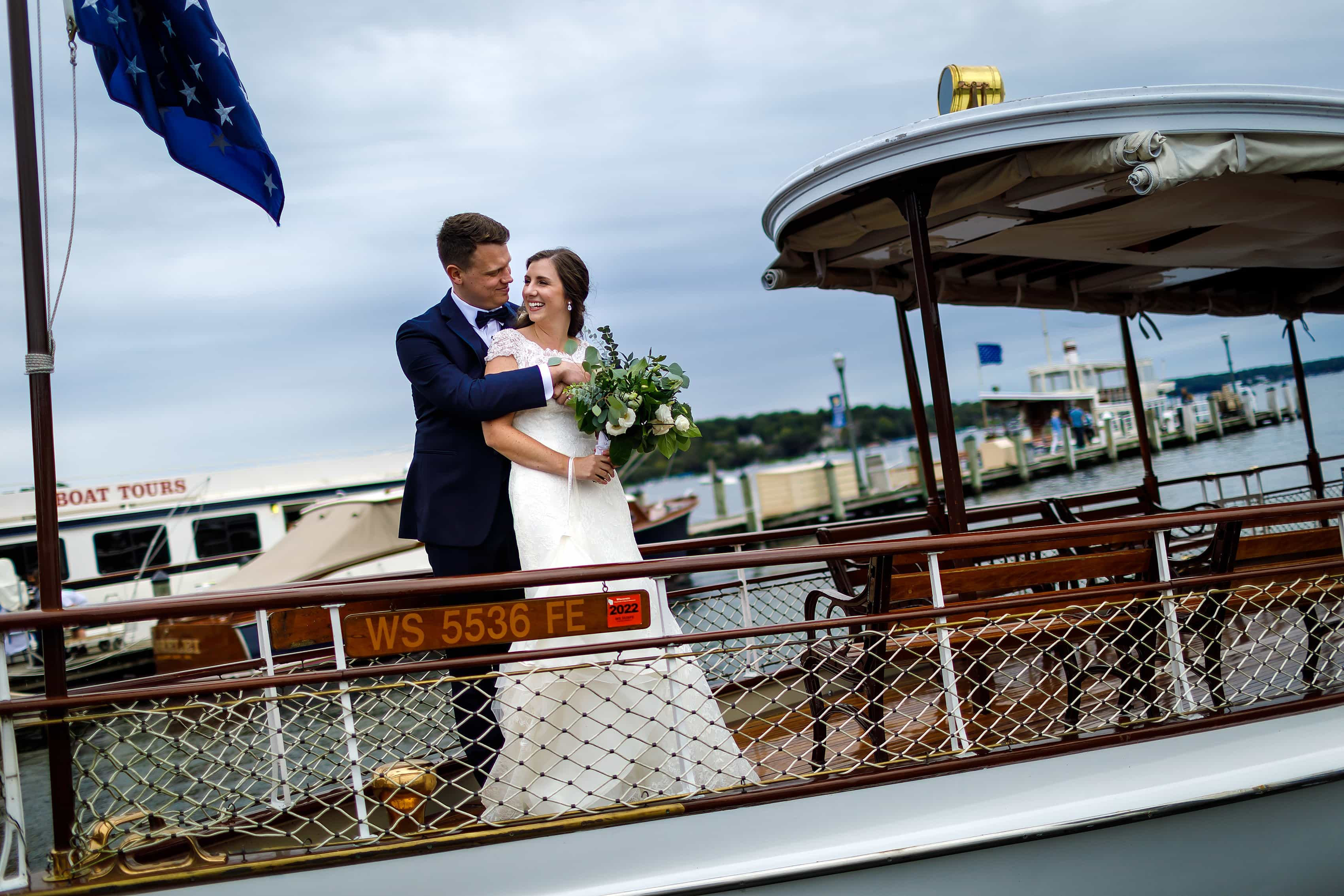 Bride and groom pose for a photo on a boat at Lake Geneva Yacht Club in Lake Geneva, Wisconsin