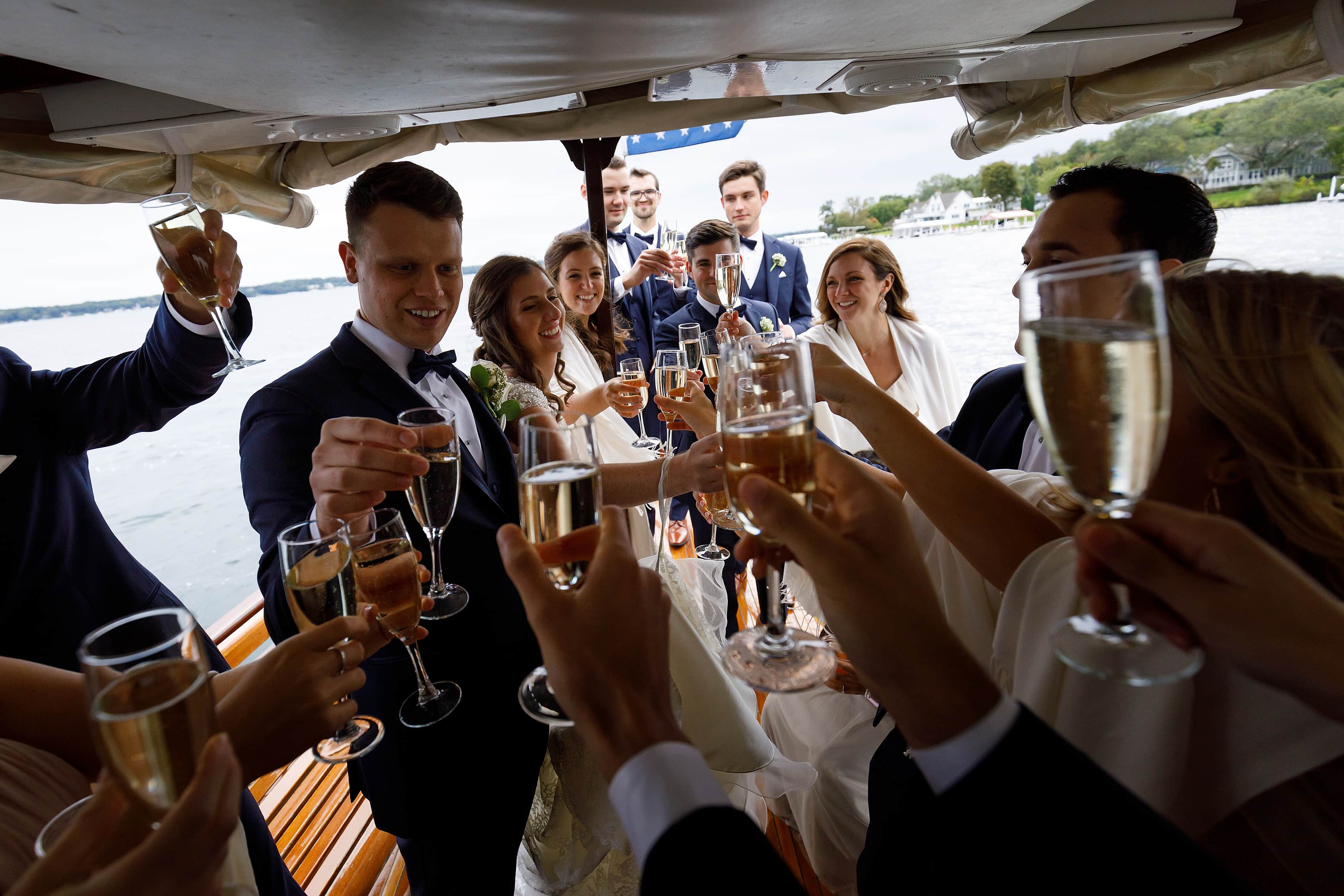 Bride and groom toast with wedding party on a boat at Lake Geneva Yacht Club in Lake Geneva, Wisconsin