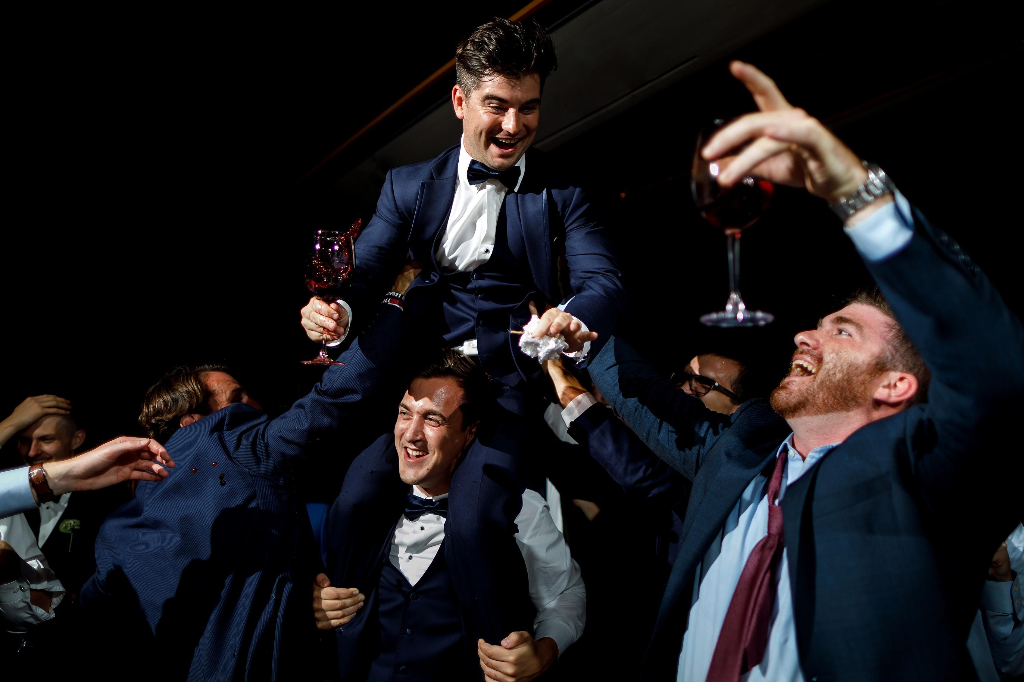 Groomsman on the shoulders of other groomsman during garter toss at wedding reception at Lake Geneva Yacht Club in Lake Geneva, Wisconsin