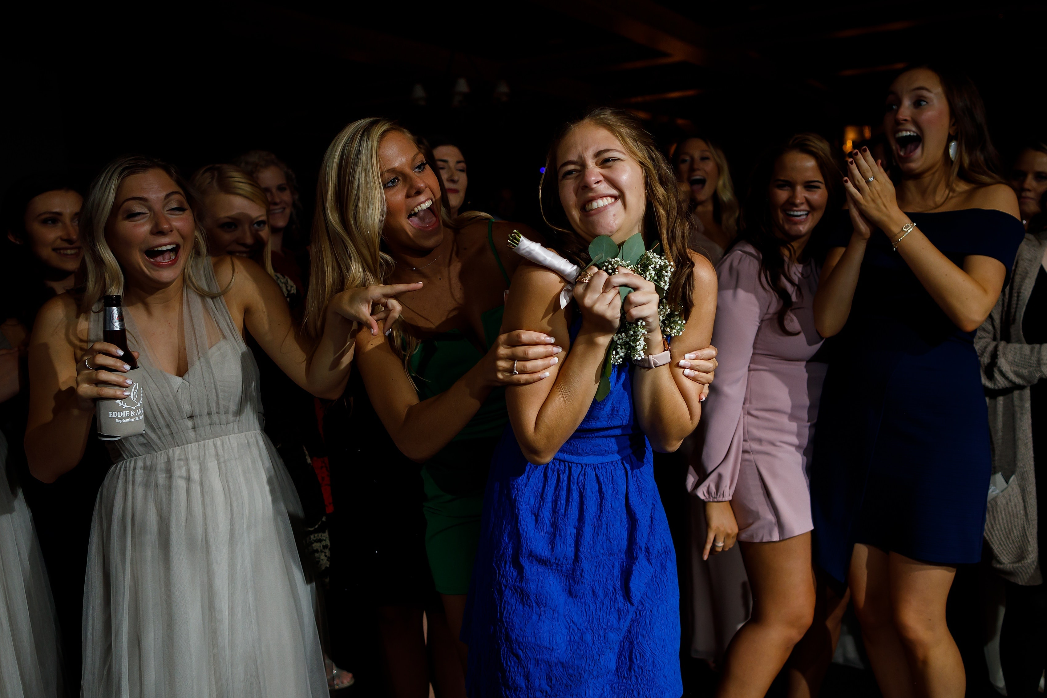 Wedding guest catches bouquet during wedding reception at Lake Geneva Yacht Club in Lake Geneva, Wisconsin