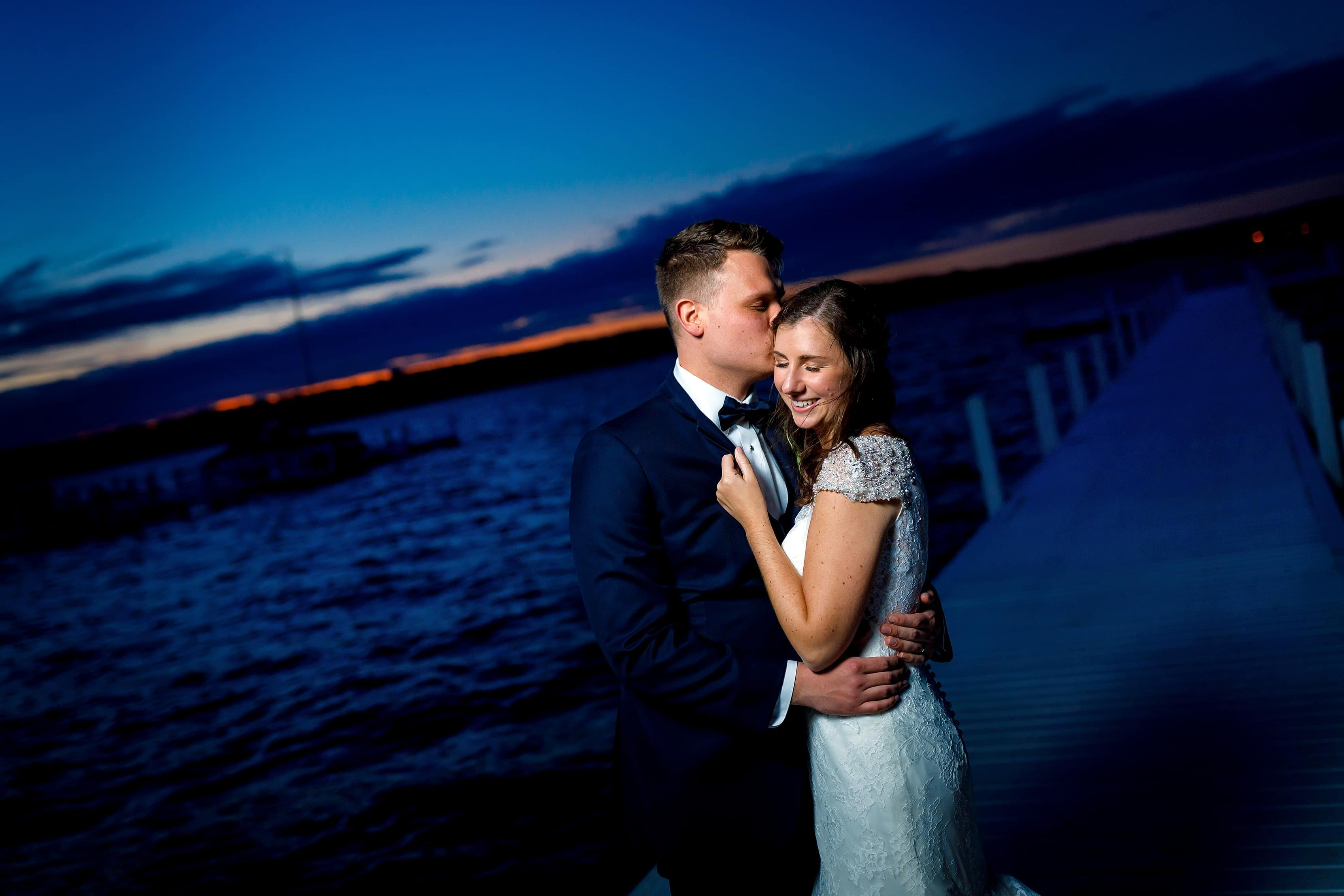 Bride and groom pose for a portrait with the sunset in the background on the dock of Lake Geneva Yacht Club in Lake Geneva, Wisconsin