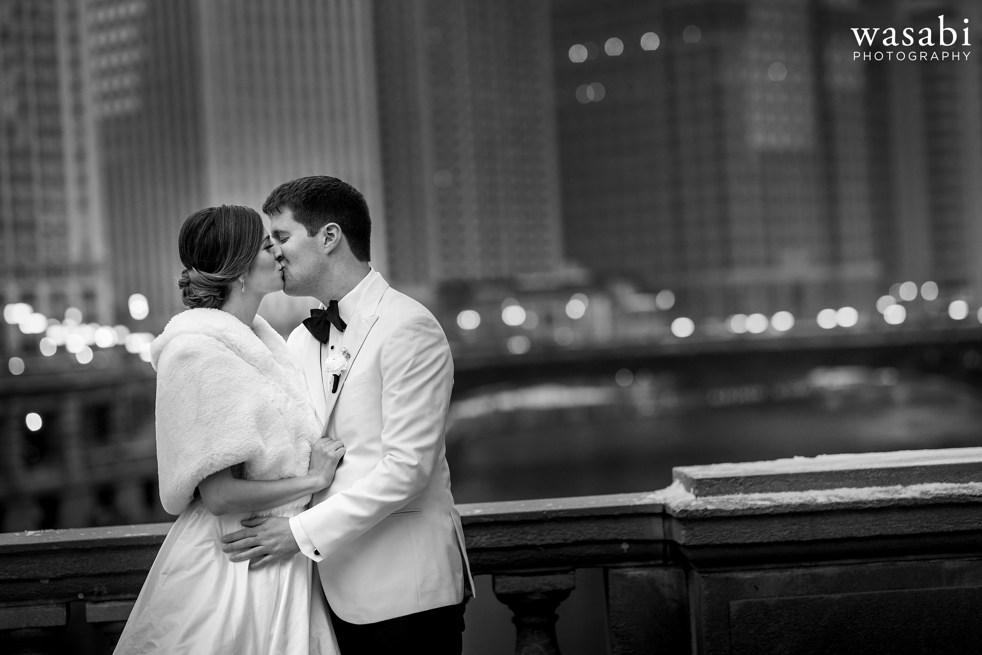 Bride and groom kiss on Michigan Ave. Bridge with Chicago River and skyline in background