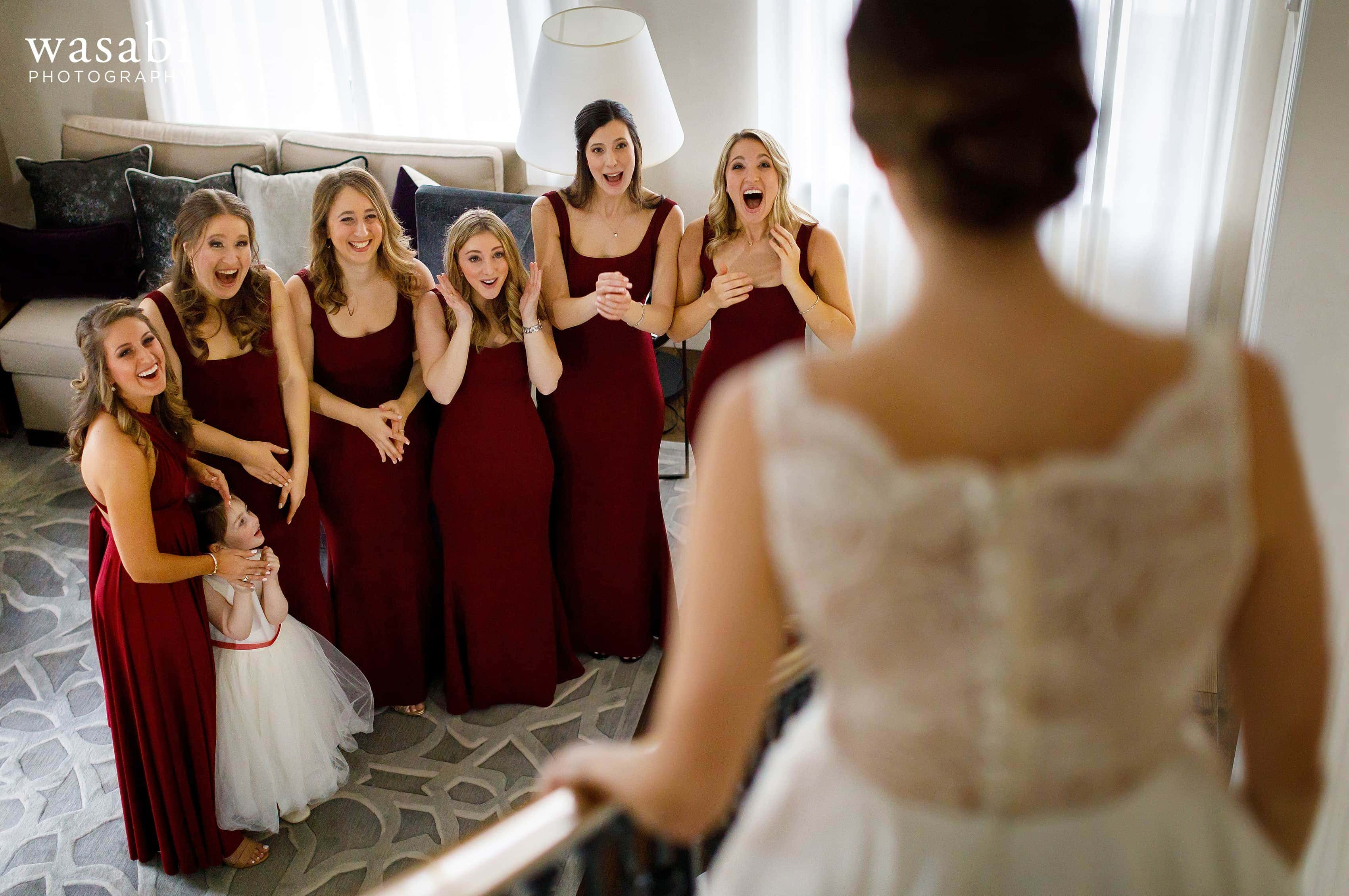 Bridesmaids react to seeing bride in wedding dress walking down the stairs in the presidential suite at InterContinental Chicago Magnificent Mile Hotel
