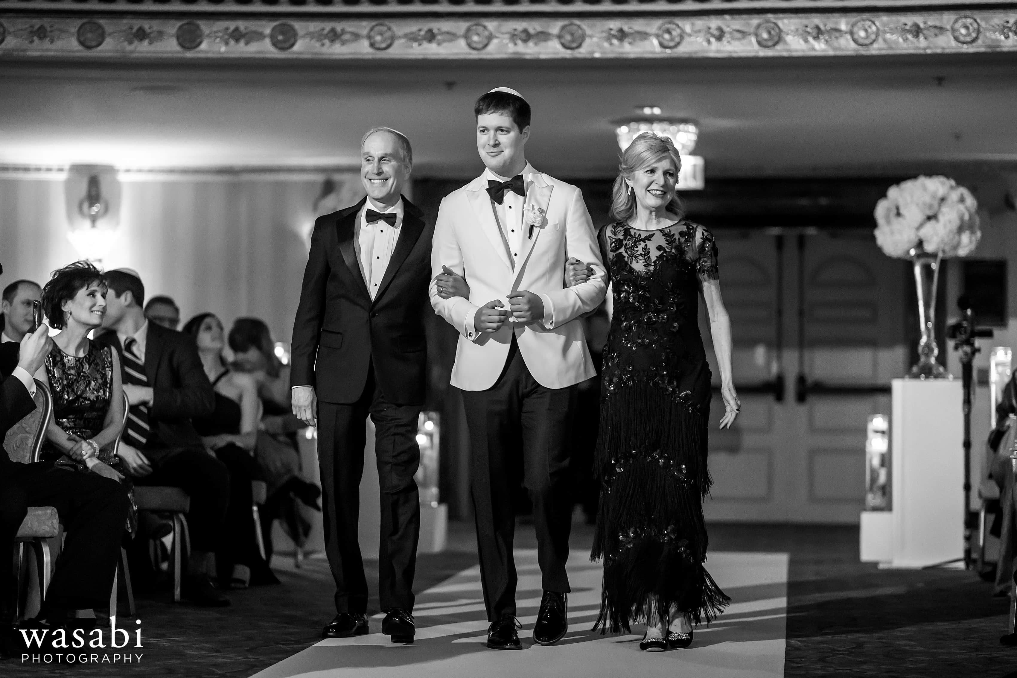Groom walks down the aisle during Jewish wedding ceremony at InterContinental Chicago Magnificent Mile Hotel