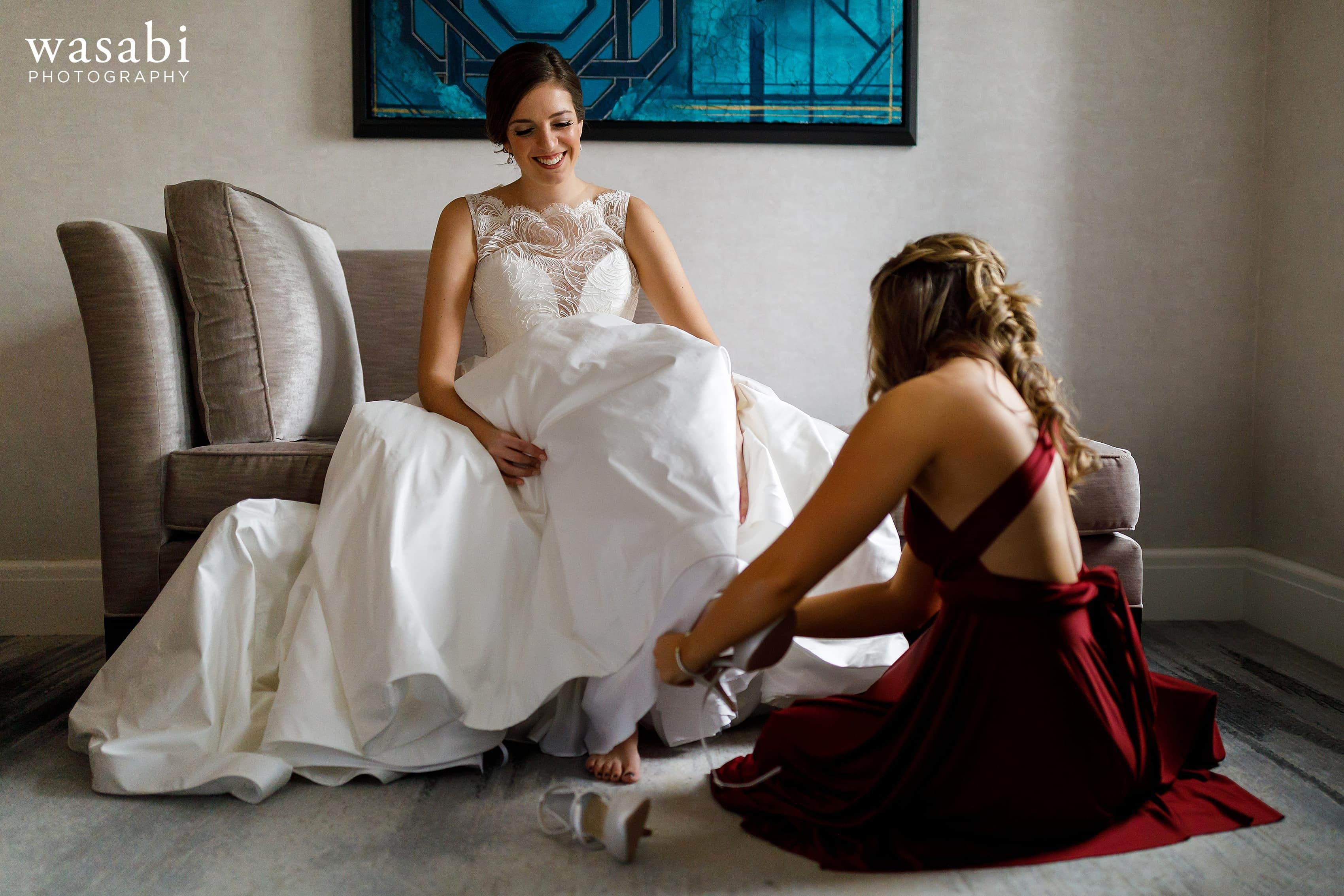 Sister helps bride with shoes while getting ready for wedding in the presidential suite at InterContinental Chicago Magnificent Mile Hotel