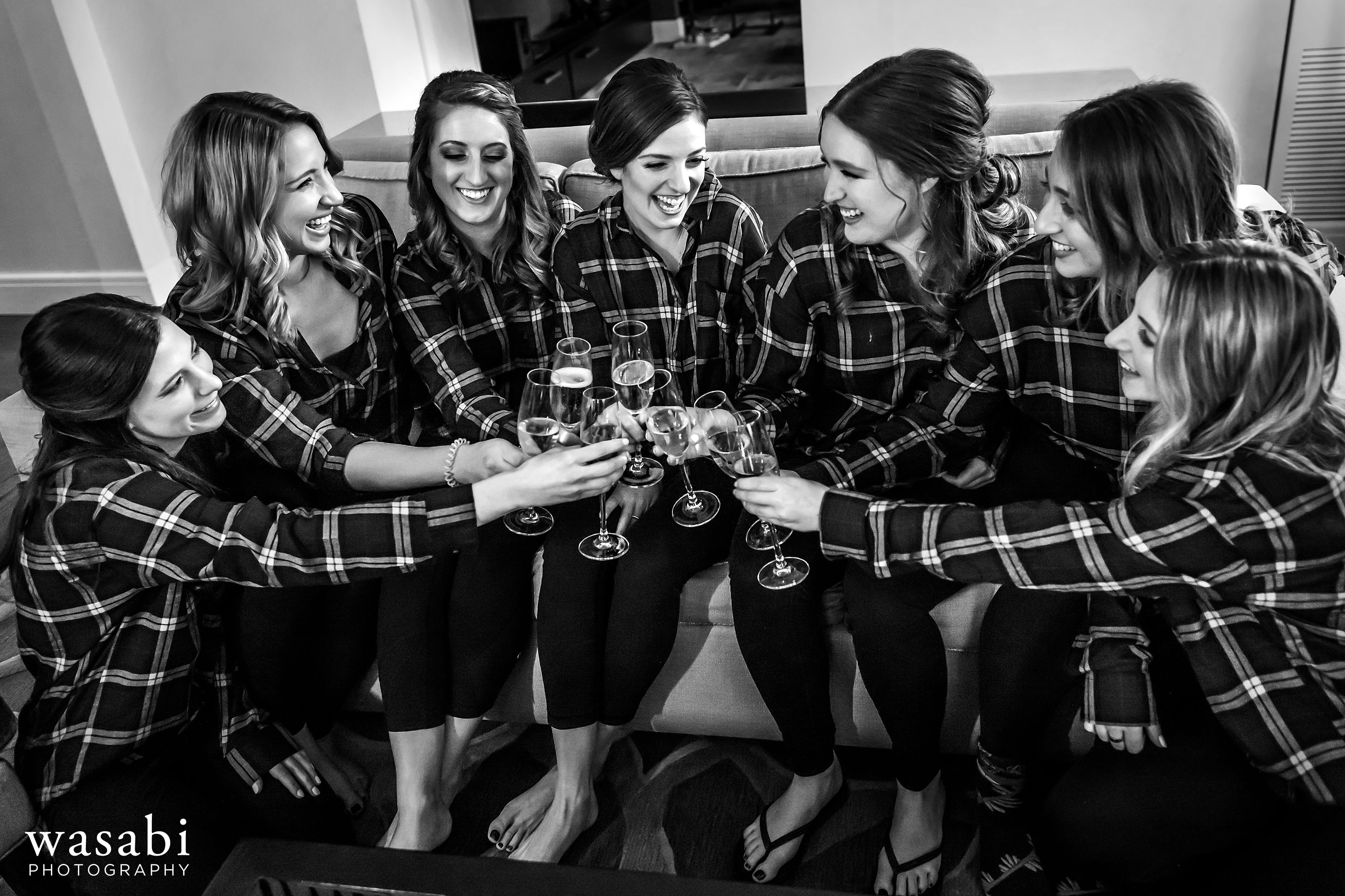 bride and many bridesmaids toast while getting ready for wedding in the presidential suite at  InterContinental Chicago Magnificent Mile Hotel